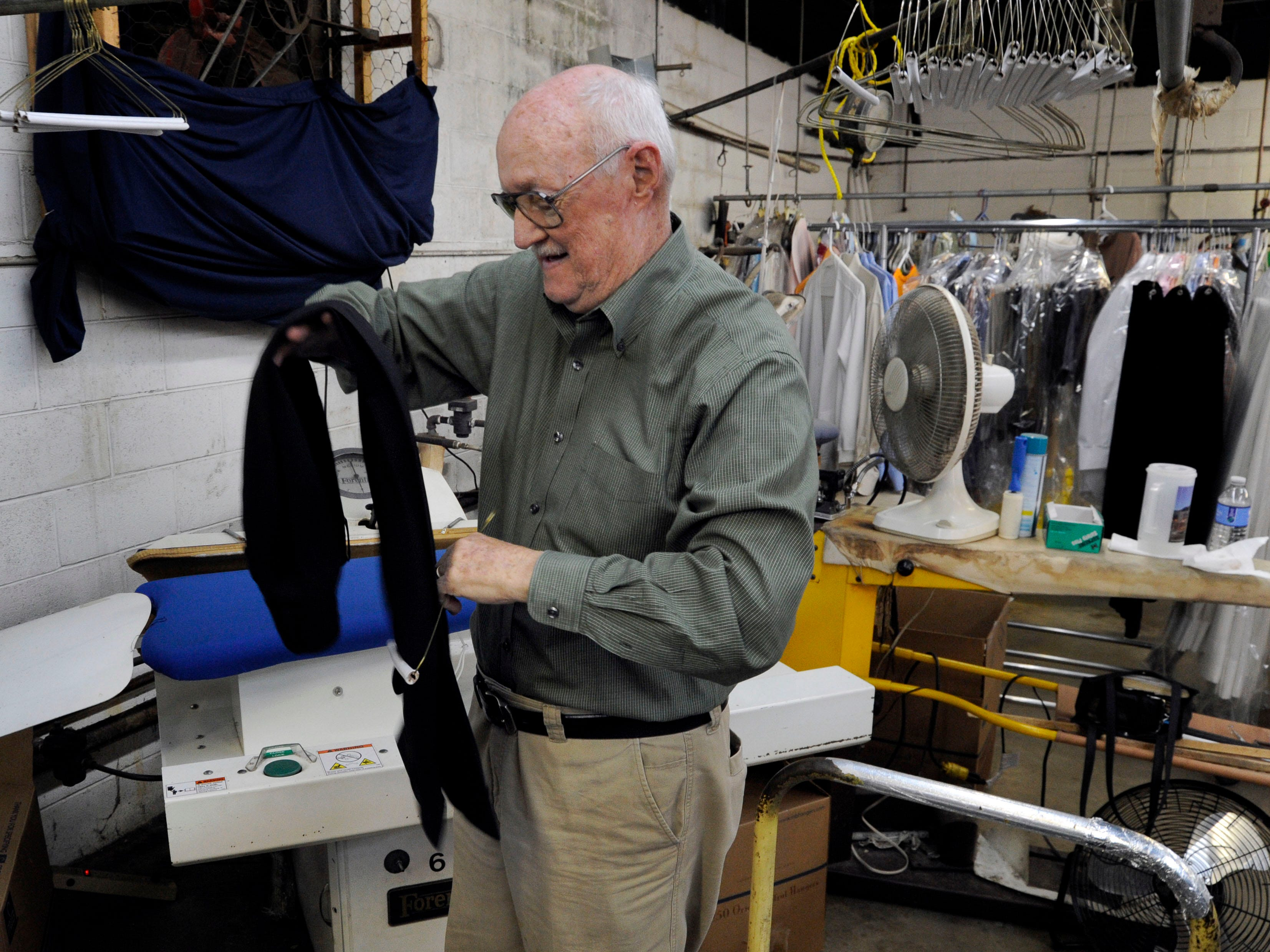 Fred T. Williams, co-owner of Knoxville Cleaners, hangs up a pair of slacks he just pressed in his store Thursday, Dec. 1, 2011. Williams said his business, in the 3000 block of Chapman Highway, is down at least 30 percent since January because of the traffic changed caused by the closing of Henley Bridge.