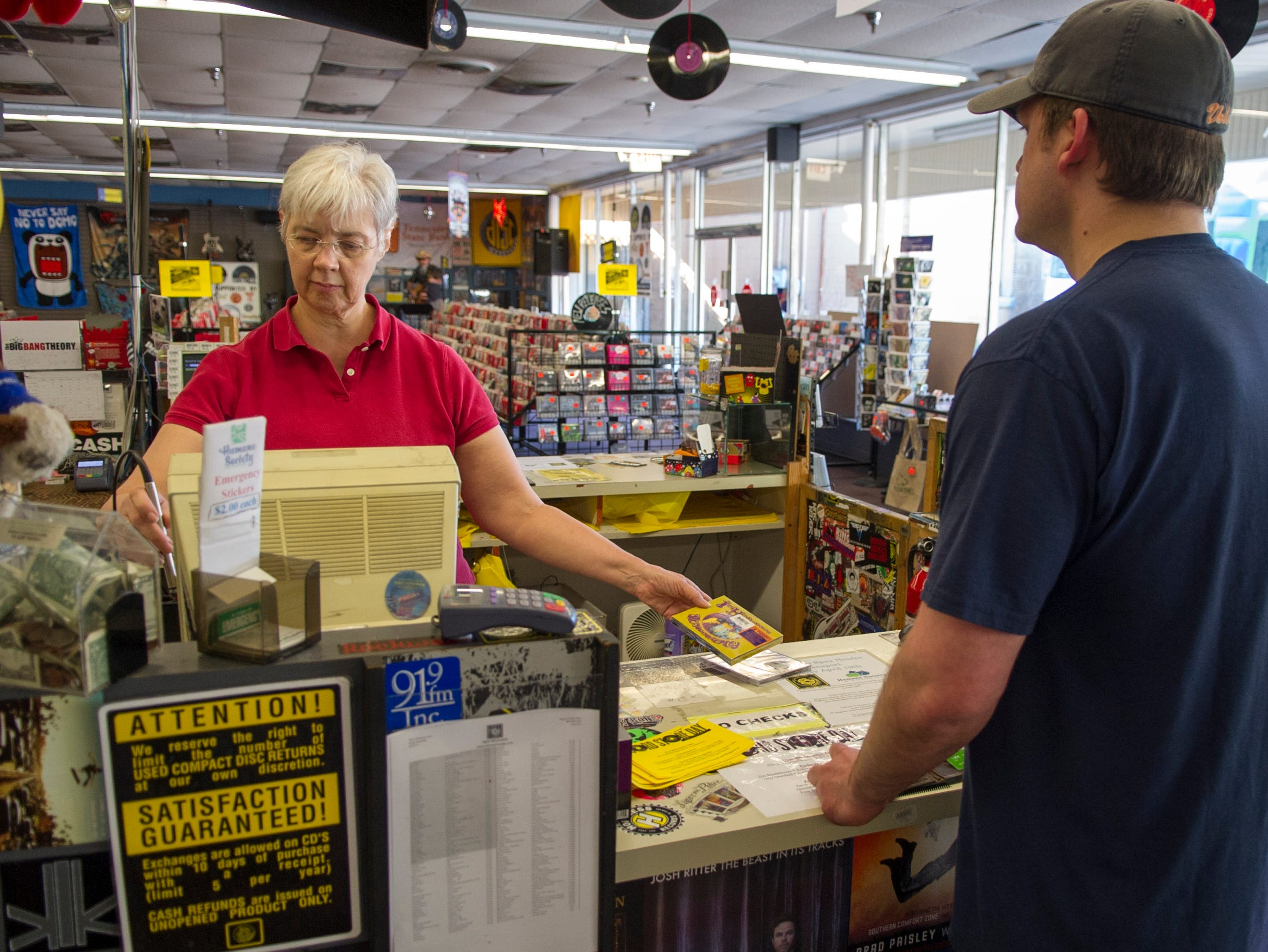 Disc Exchange co-owner Jennie Ingram, left, helps customer Dustin Johnson, right, with a purchase at the store on Chapman Highway in South Knoxville Friday, April 12, 2013. SouthFest takes place this weekend featuring live music at the store and festivities in the nearby parking lot and along Chapman Highway.
