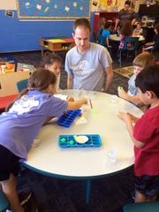 Zack Kennard gets a table filled with kindergartners and first graders started on a project to make bouncy balls.