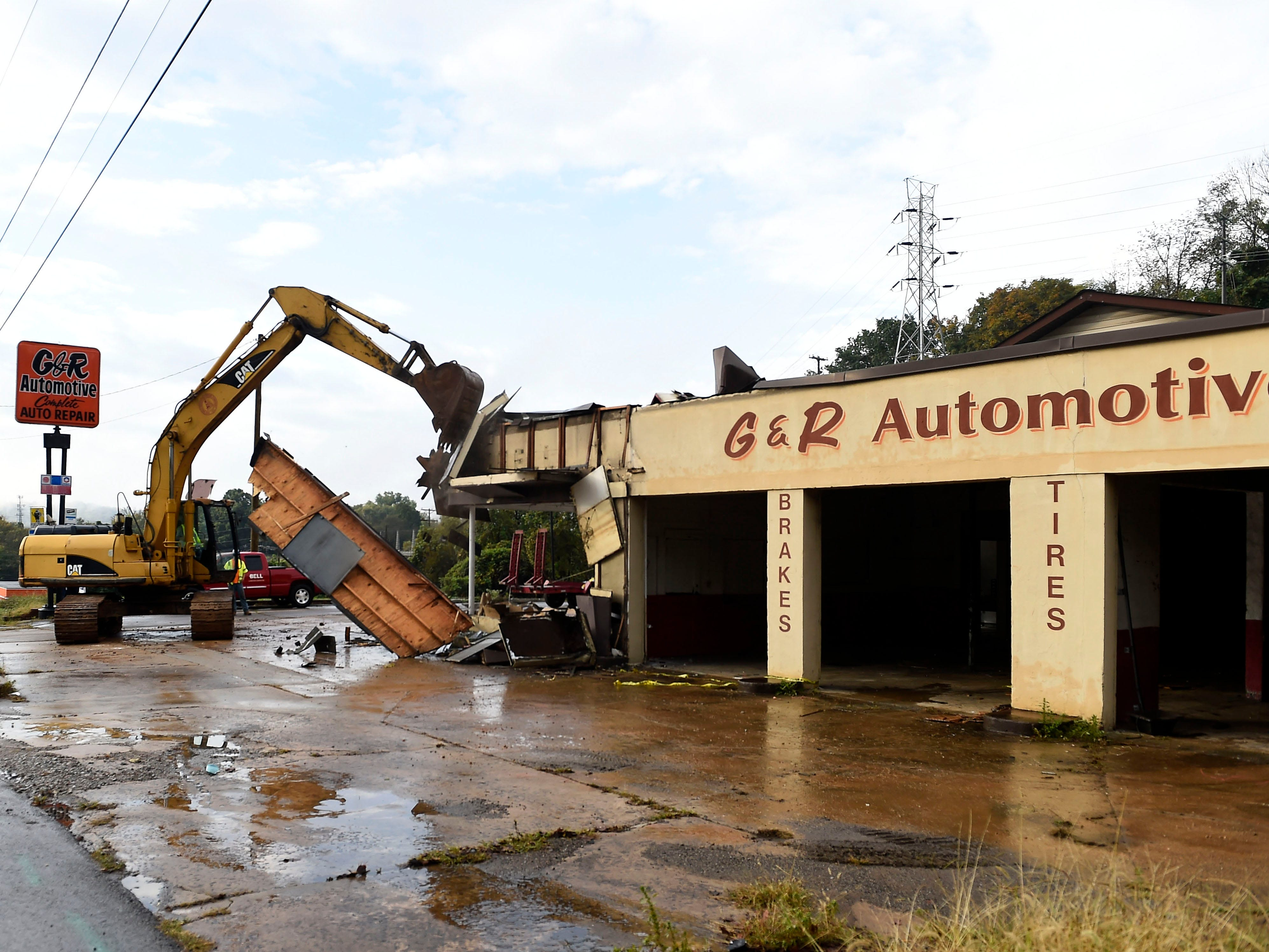 Employees with Bell Construction begin demolition on G&R Automotive on Chapman Highway on Monday, Oct. 13, 2014 in Knoxville, Tenn. The demolition will allow for construction of a new entryway into Fort Dickerson Park.
