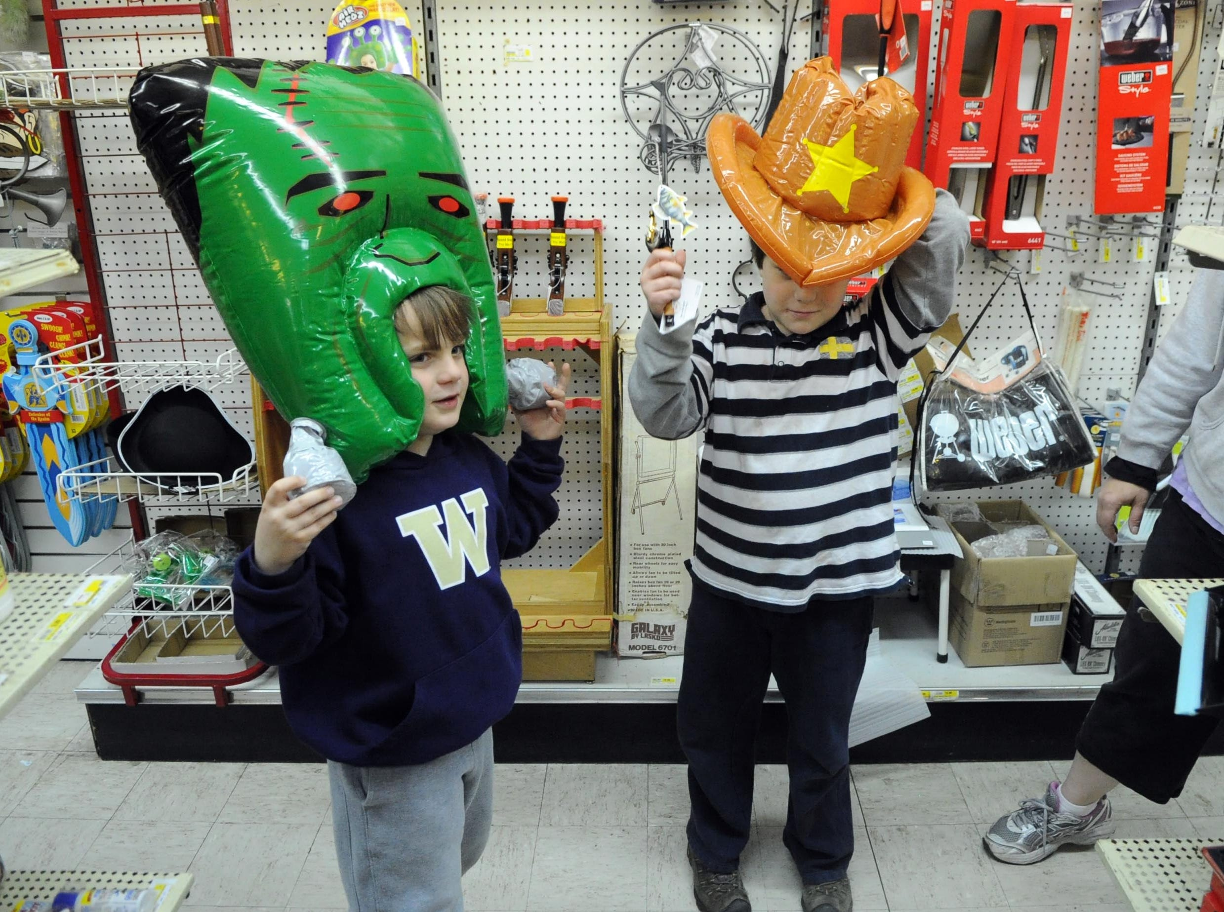 "Braxxton (cq) and Boone Sommers, left to right, try on costumes during the ""Cash Mob"" at Emery's 5&10 on Chapman Highway in South Knoxville Friday, Feb. 10, 2012."