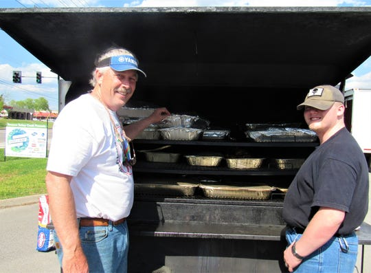 Volunteers Stuart Rowe and Hugh Koch tended the grill last year at the Feeding God's Children Chicken and Rib Roast.