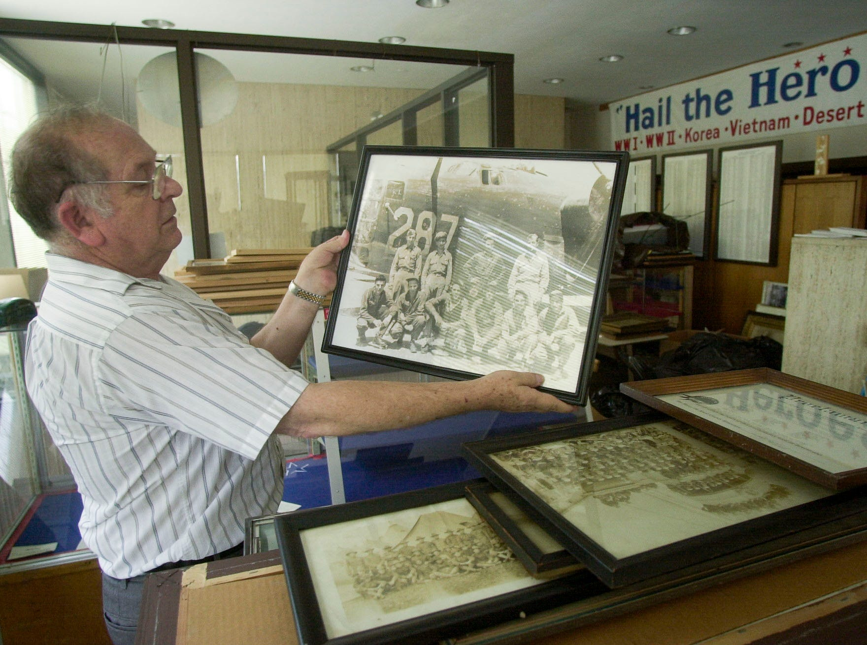 Museum founder Arnold R. Mullins pauses with a photograph of a World War II bomber crew while packing boxes Thursday at the Tennessee Veterans Hall of Honor & Honor Guard Museum at 4000 Chapman Highway. Over 2,000 artifacts are going into temporary storage until a new home can be found for the museum's collection.