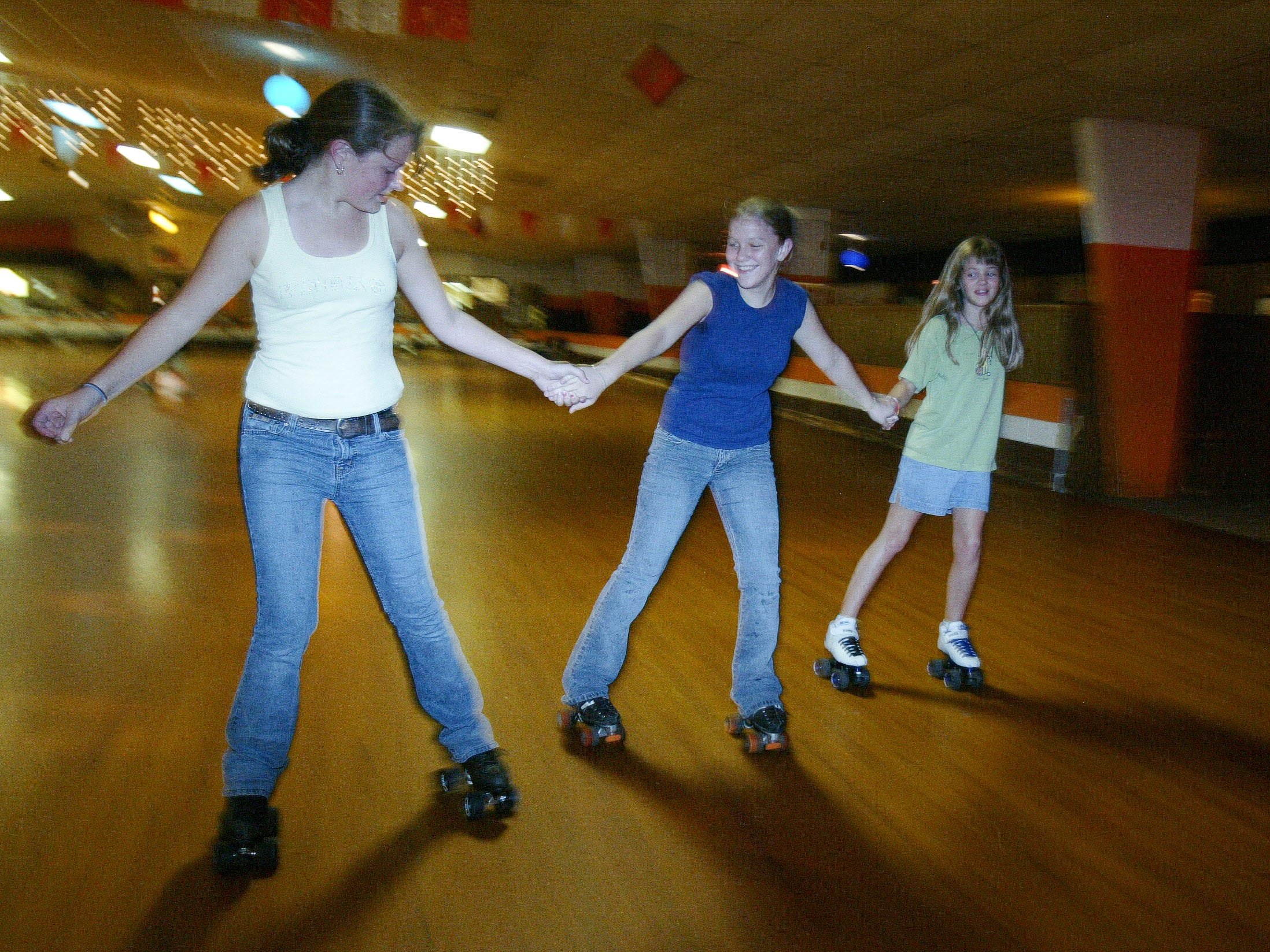 Kacy Adkins, left, Tiffany Brewer and Amanda Adkins take a spin around the roller rink at Tennessee Valley Skate Center on Chapman Highway on August 26, 2005. The family-owned skating rink closed for business on Aug. 20 after 28 years.
