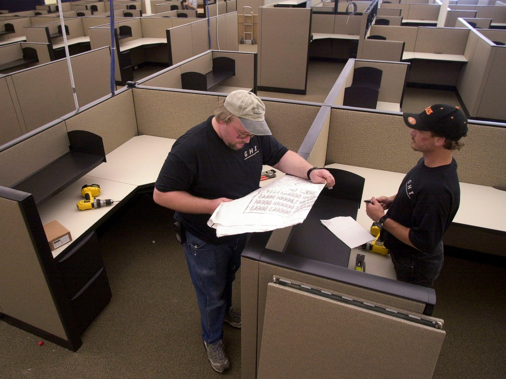 Rodger Ritter, left, and Jeff Bertram install cubicles at the Nova Information Systems expansion Friday in South Knoxville. Nova is expanding into a 60,000 sq. ft.  building on Chapman Highway that was the former Lowe's Home Improvement Warehouse. The new facility will house 400 new employees according to Executive VP David Strider. 2003.