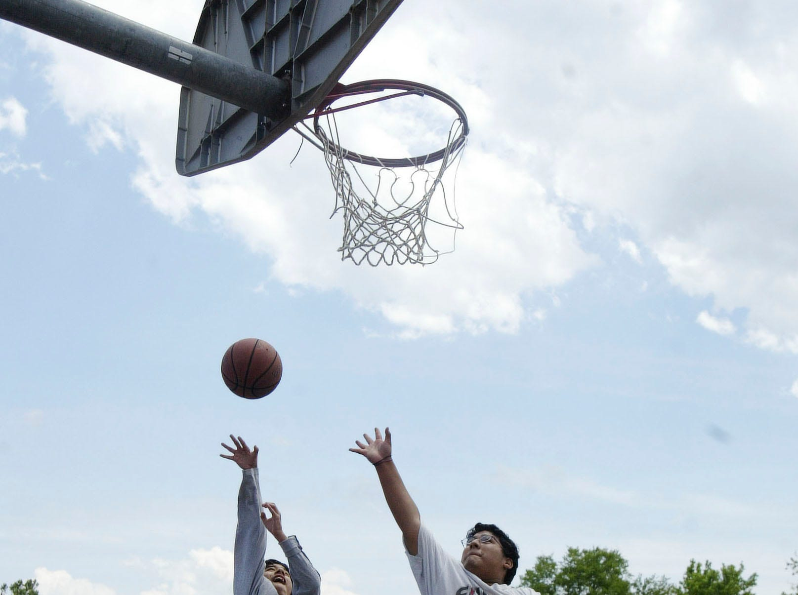 Brian Martinez, 12, shoots over the outstretched arm of his brother David, 16, at the Sam Duff Memorial Park located off Chapman Highway in May 2005.