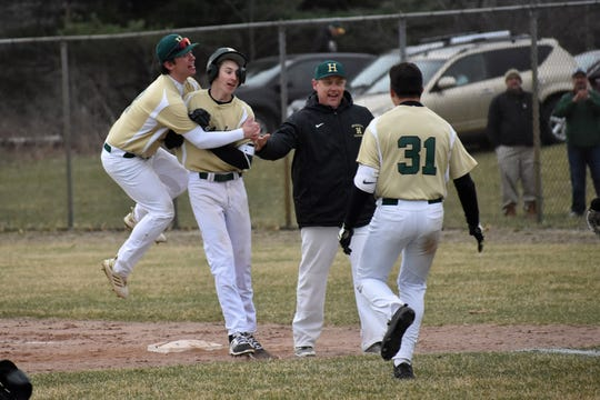 Nick Austin hugs Howell teammate Adam Mrakitsch after Mrakitsch hit a game-winning single in the eighth inning against Brighton on Wednesday, April 10, 2019.