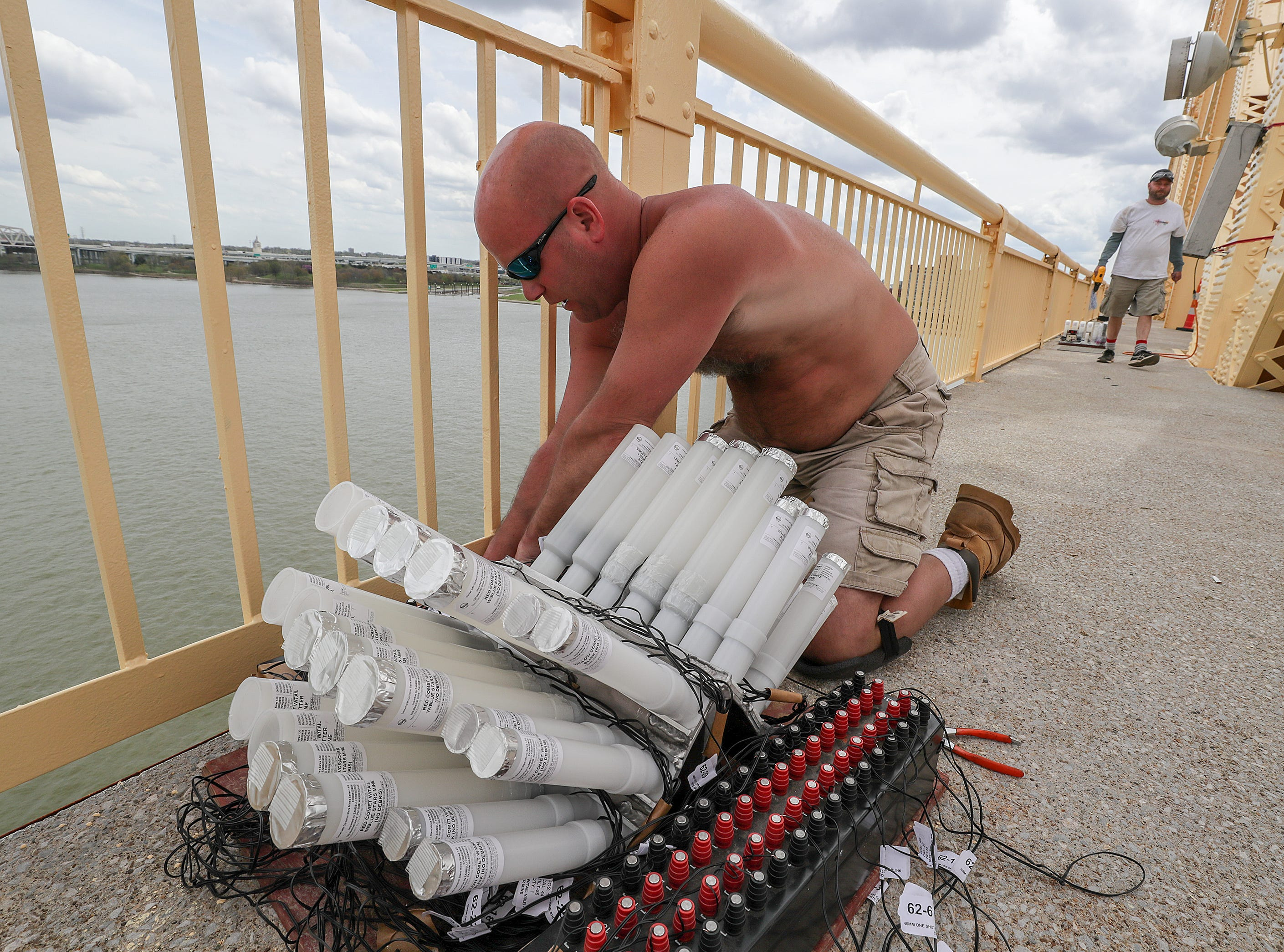 Michael Myers, with Zambelli, helps secure the fireworks to the Clark Memorial Bridge on Thursday afternoon as crews took over the bridge in advance of Thunder Over Louisville.
