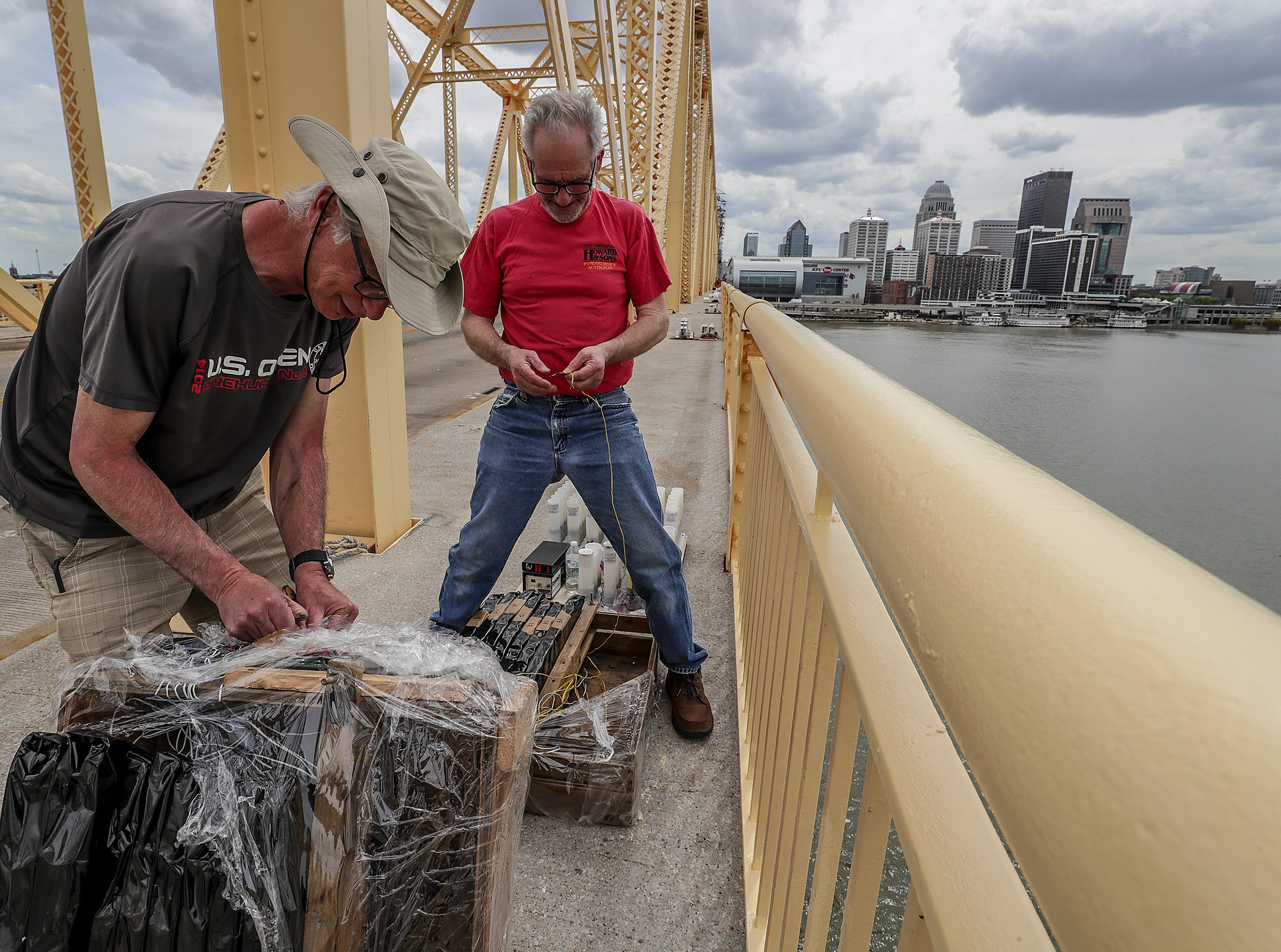 Stuart Schwartz and mark Wilson, with Zambelli, help secure the fireworks to the Clark Memorial Bridge on Thursday afternoon as crews took over the bridge in advance of Thunder Over Louisville.