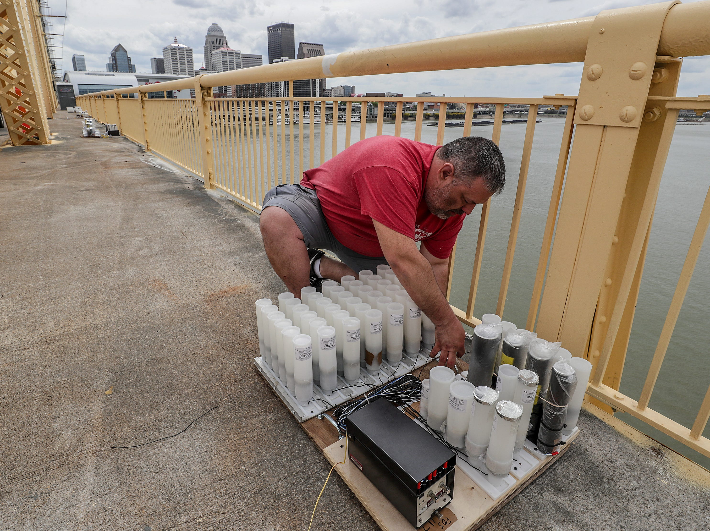Jeremy Rudesill, with Zambelli, helps secure the fireworks to the Clark Memorial Bridge on Thursday afternoon as crews took over the bridge in advance of Thunder Over Louisville.