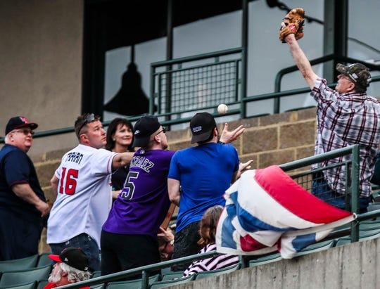 Fans reach for a foul ball at Thursday night's Louisville Bats season opener.