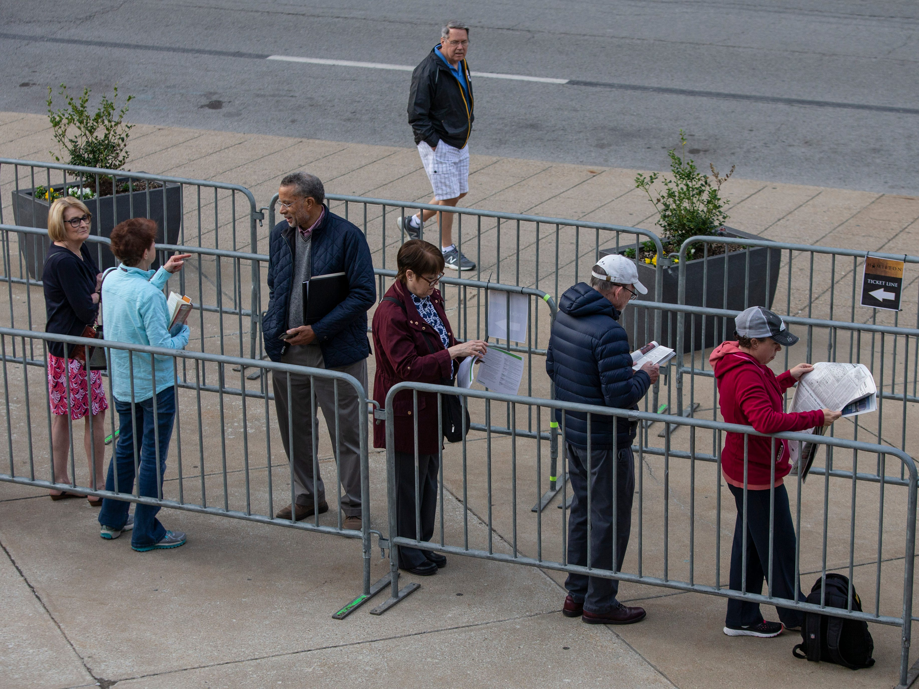 """People waiting in line for tickets to """"Hamilton"""" occupied their time reading the books, the newspaper and taking to others in line. April 11, 2019."""