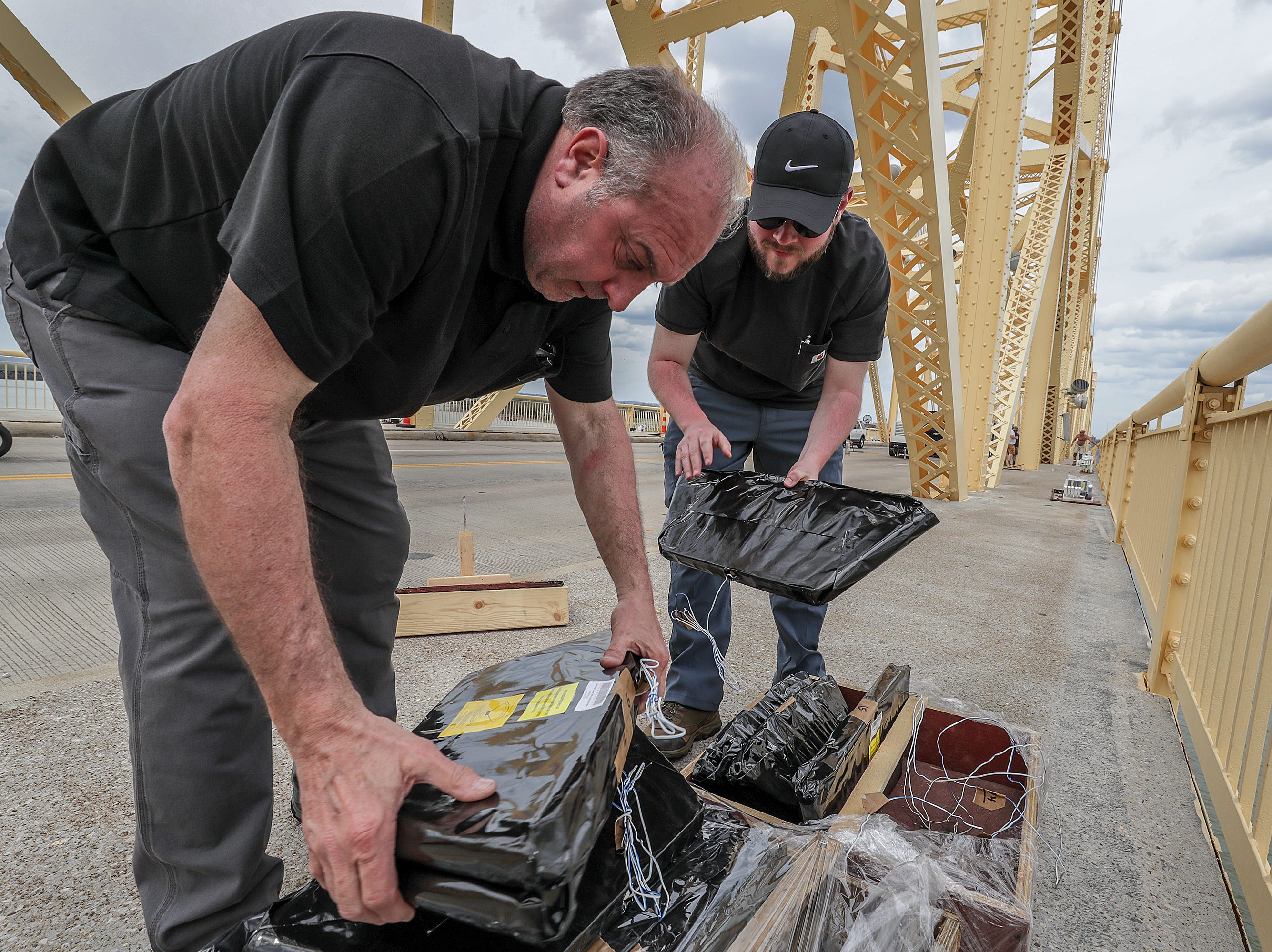 Ralph Piacquadio and David Hunter, with Zambelli, co-designers of the fireworks display for Thunder over Louisville, work to place displays on the Clark Memorial Bridge on Thursday afternoon.