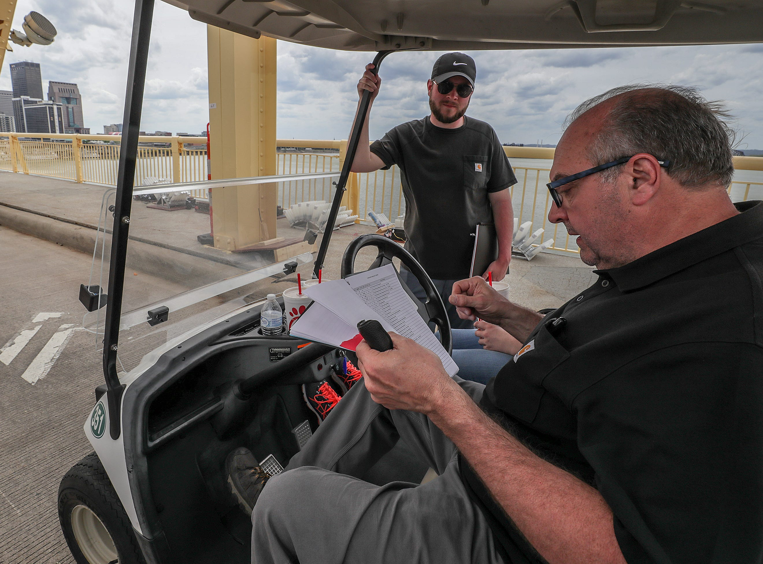 Ralph Piacquadio and David Hunter, with Zambelli, co-designers of the fireworks display for Thunder over Louisville, look over notes as crews begin to place fireworks along the Clark Memorial Bridge on Thursday afternoon.