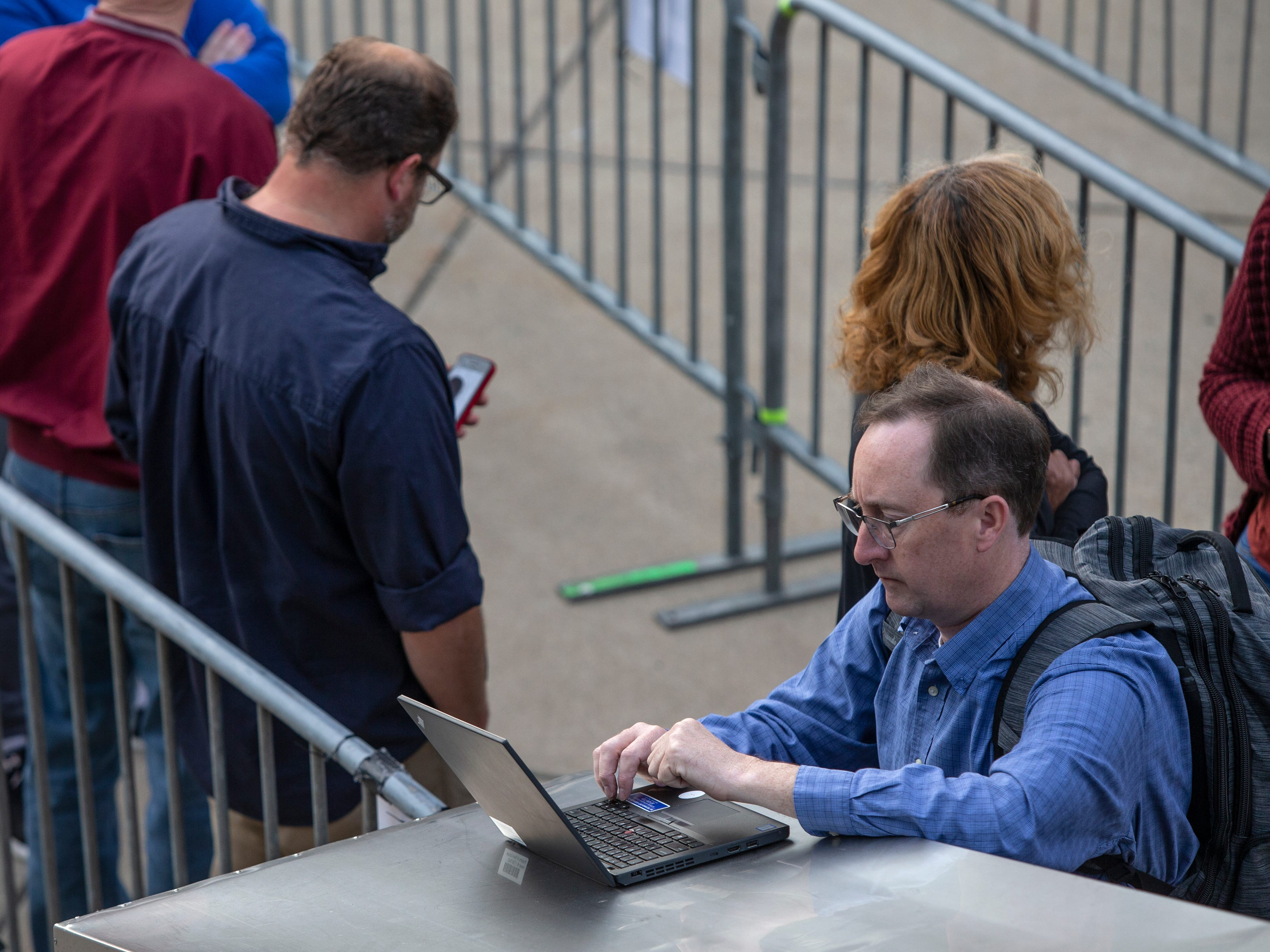 """Jim Williams works on employee performance appraisals while waiting in line for tickets to the play, """"Hamilton."""" April 11, 2019."""