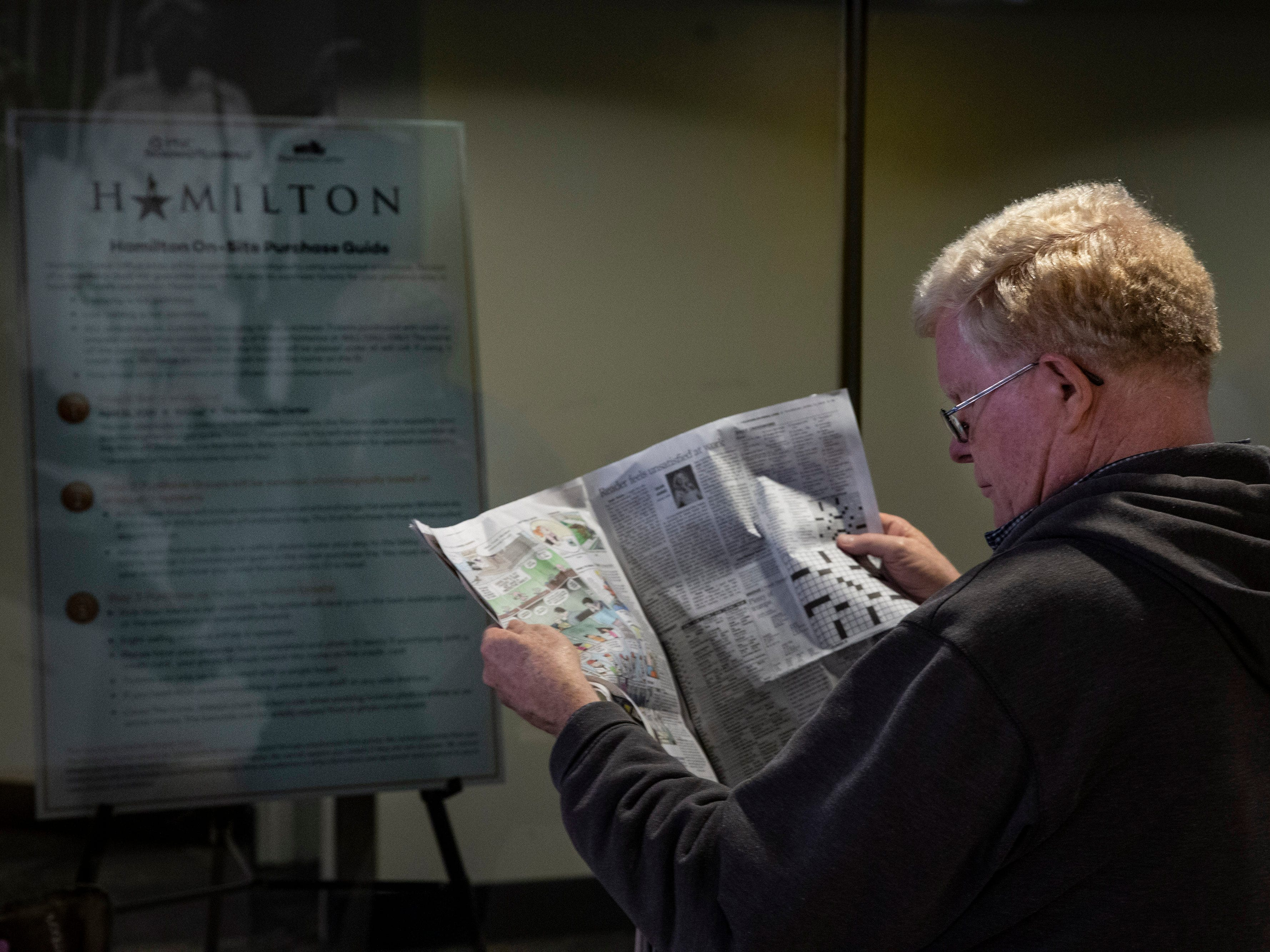 """John Hayens read the Courier Journal while waiting in line for tickets to the play, """"Hamilton,"""" at the Kentucky Center for the Arts. Haynes arrived at the center at 6:45 to join the line of people. April 11, 2019."""