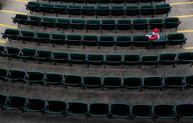 A boy in a Cincinnati Red hat -- the parent club to the Louisville Bats -- waits in his seat before the Louisville Bats season opener Thursday night at Slugger Field. April 11, 2019
