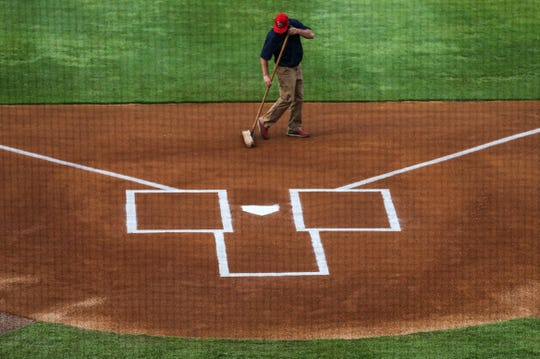 A groundskeeper grooms the dirt in front of the batter's box before the Louisville Bats season opener.