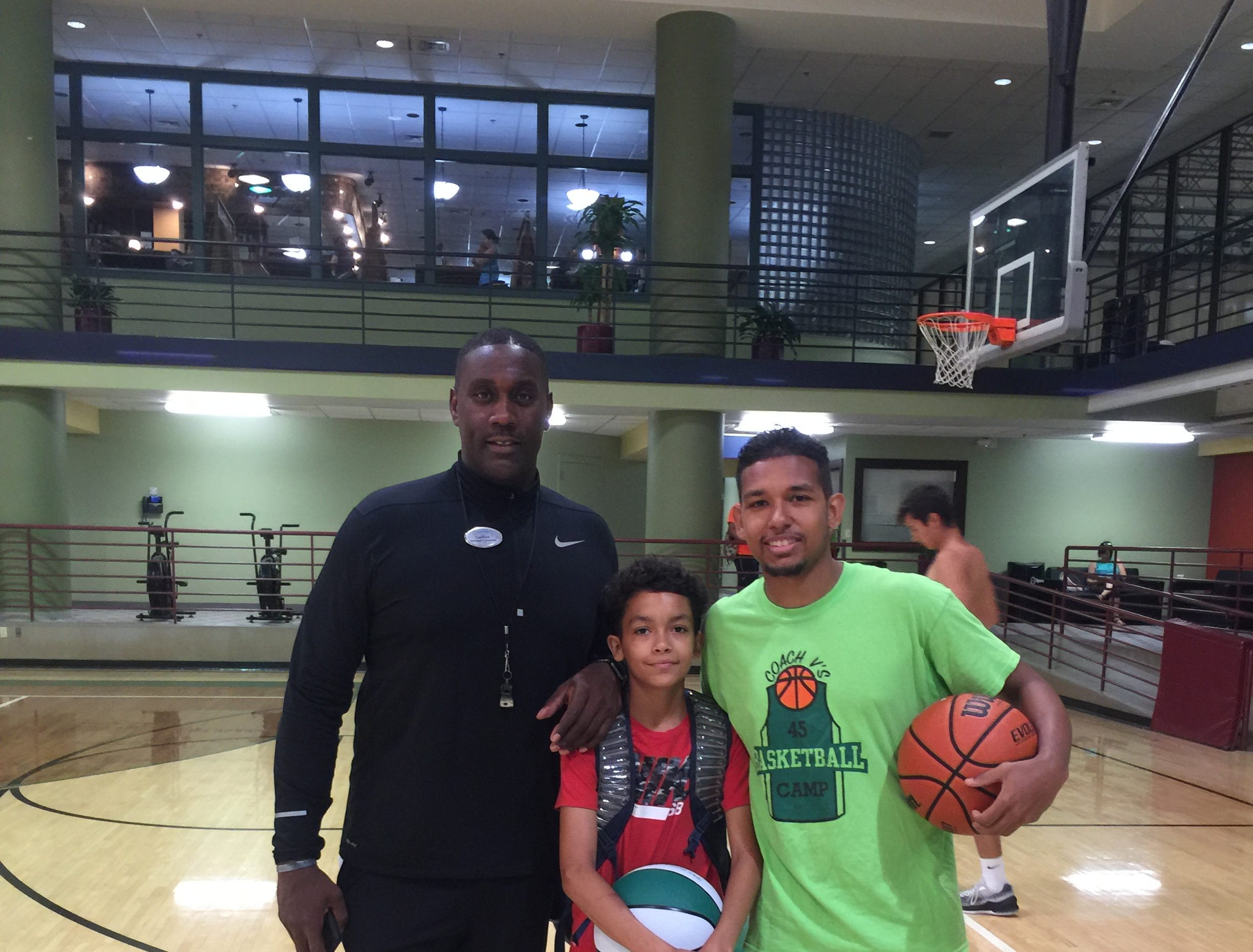 Robert Ray Jr., right, poses for a photo with basketball camp attendee Cameron Lower and his former high school basketball coach, Carlton Valentine.