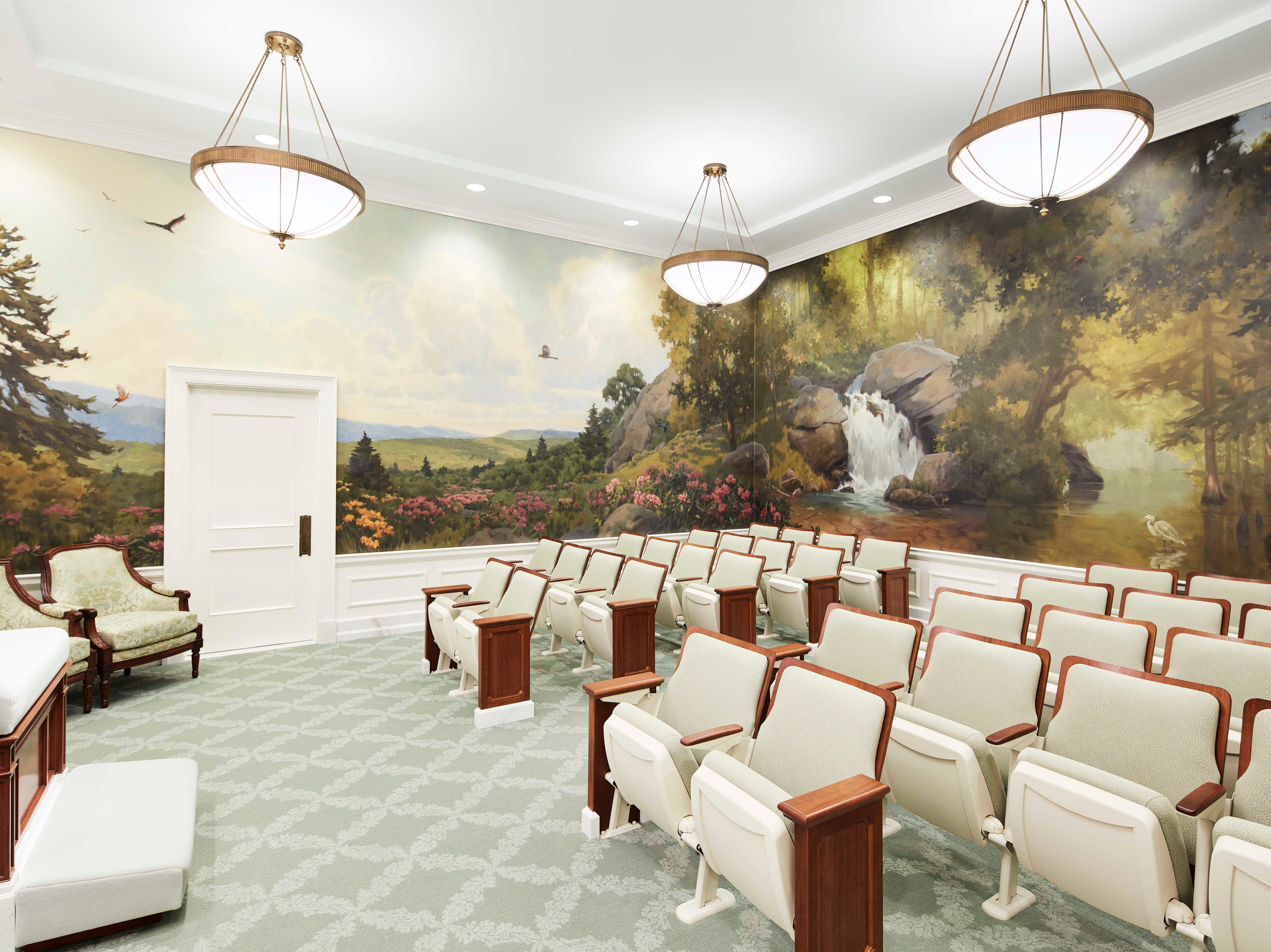 An instruction room in the newly renovated Memphis Tennessee Temple has an altar in the front. Around the walls is a mural featuring a landscape painting.