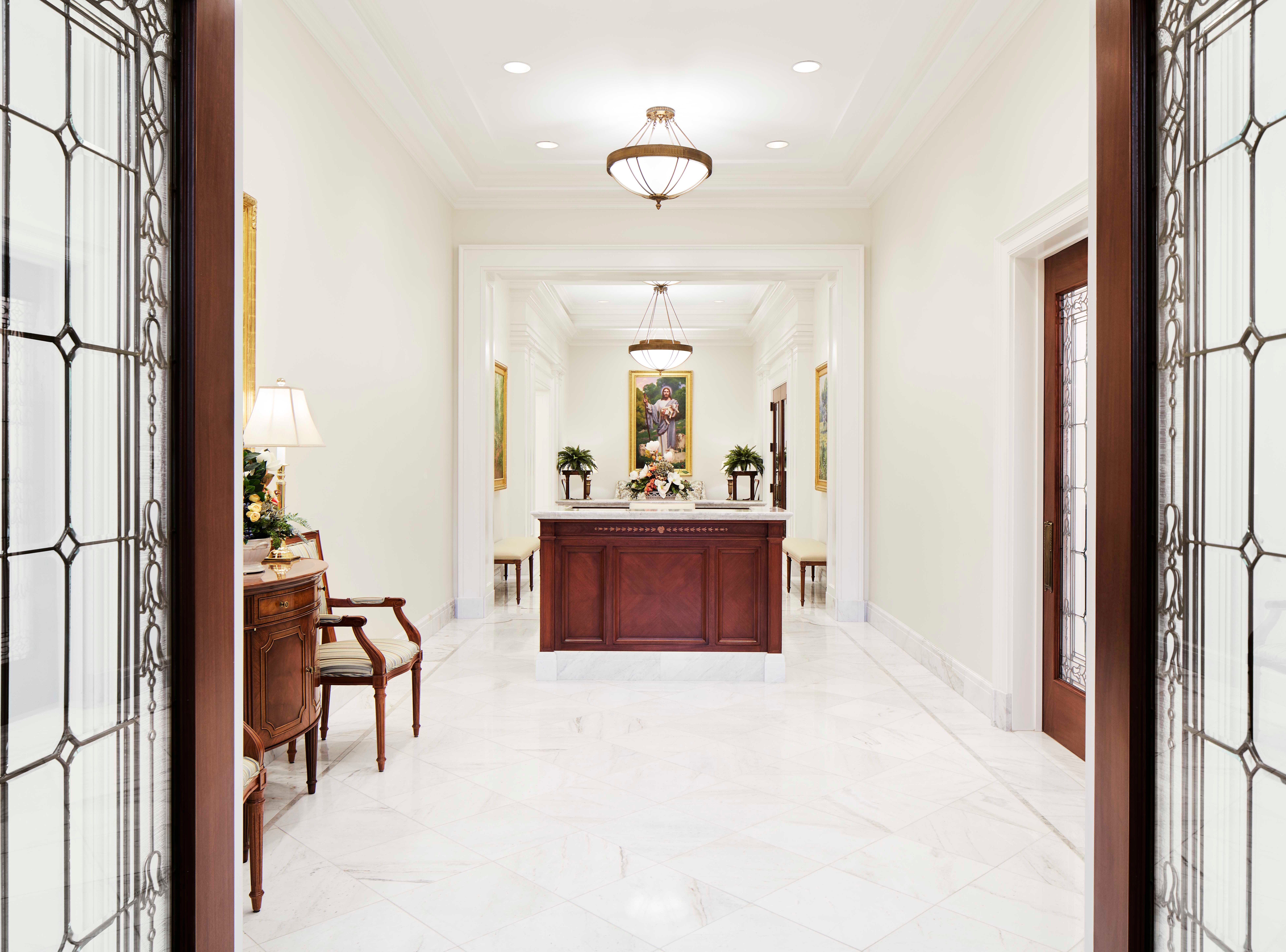 Walking through the front doors of the Memphis Tennessee Temple, people are greeted with a front desk and a painting of Jesus as a shepherd, holding a lamb.