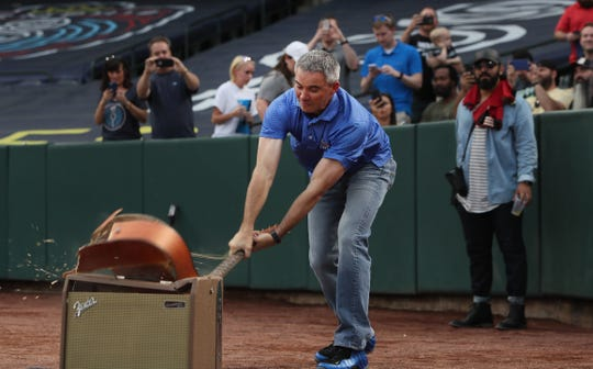 University of Memphis Head Football Coach Mike Norvell smashes a guitar to kick off the start of the Memphis 901 FC game against Atlanta United 2 at AutoZone Park on Wednesday, April 10, 2019.