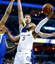Memphis Grizzlies guard Jevon Carter (bottom) drives for a layup against Golden State Warriors defender Klay Thompson (top) during action at the FedExForum in Memphis, Tenn., Wednesday, April 10, 2019.