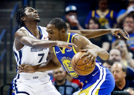 Memphis Grizzlies defender Justin Holiday (left) applies defensive pressure against Golden State Warriors forward Kevin Durant (right) during action at the FedExForum in Memphis, Tenn., Wednesday, April 10, 2019.