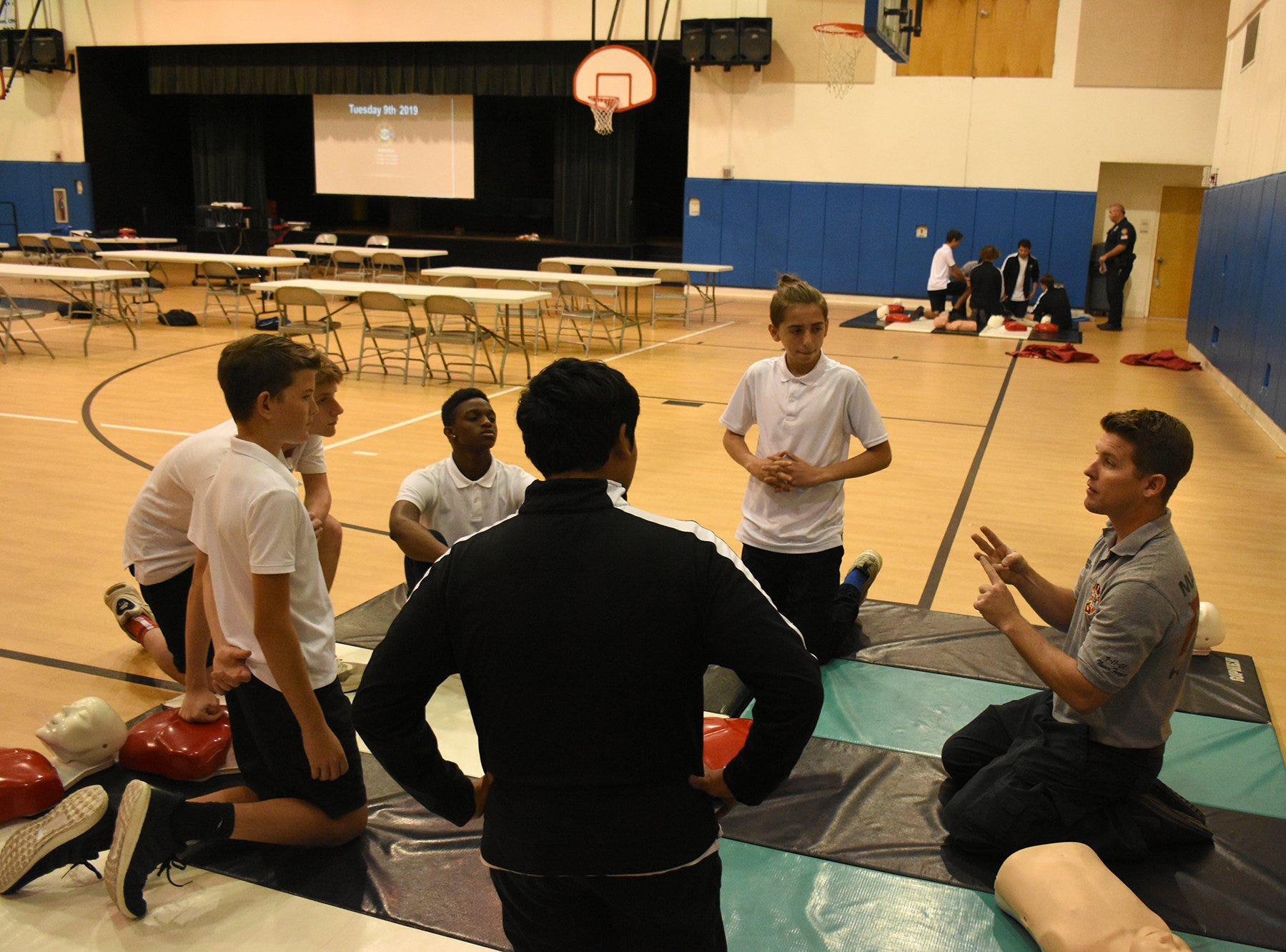 Firefighter/paramedic Chris Bowden works with students. The Marco Island Fire-Rescue Dept. trained all eighth graders at MICMS in CPR technique this week.