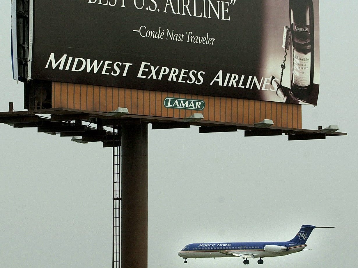A Midwest Express flight lands in 2001 at Mitchell International Airport under a sign touting the airlines ranking by Conde´Nast Traveler. Layoffs at the airline had been announced earlier.