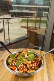 Sriracha peanut fries are a shareable appetizer served at Punch Bowl Social, 1122 N. Vel R. Phillips Ave. Some of the tables come with a view of Fiserv Forum, home of the Milwaukee Bucks, across the pedestrian plaza from the restaurant-bar-and-bowling-karaoke-game emporium.