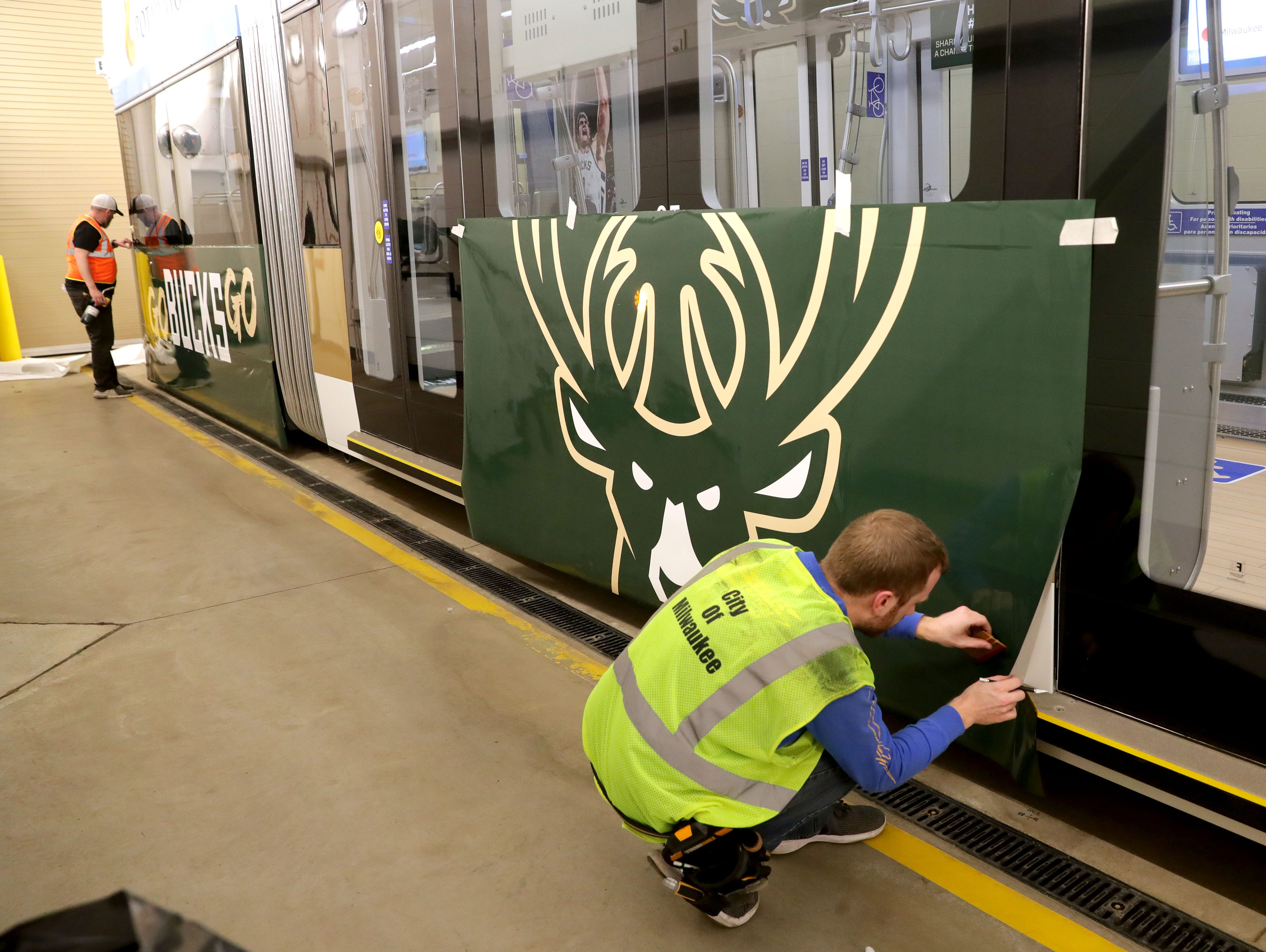 (OK FOR FRIDAY 4/12 PRINT - ONLINE EMBARGO UNTIL 10:45 FRIDAY 4/12)Troy Heinzel with Signs and Lines by Stretch work on attaching a logo to the outside of the streetcar.  One of Milwaukee's streetcars, known as The Hop is wrapped in Milwaukee Bucks colors in support of the Bucks playoff run in Milwaukee on Thursday, April 11, 2019. In addition to the exterior flair, the interior has been fitted with a replica Bucks court on the floor complete with life-size player footprints.   Photo by Mike De Sisti/Milwaukee Journal Sentinel