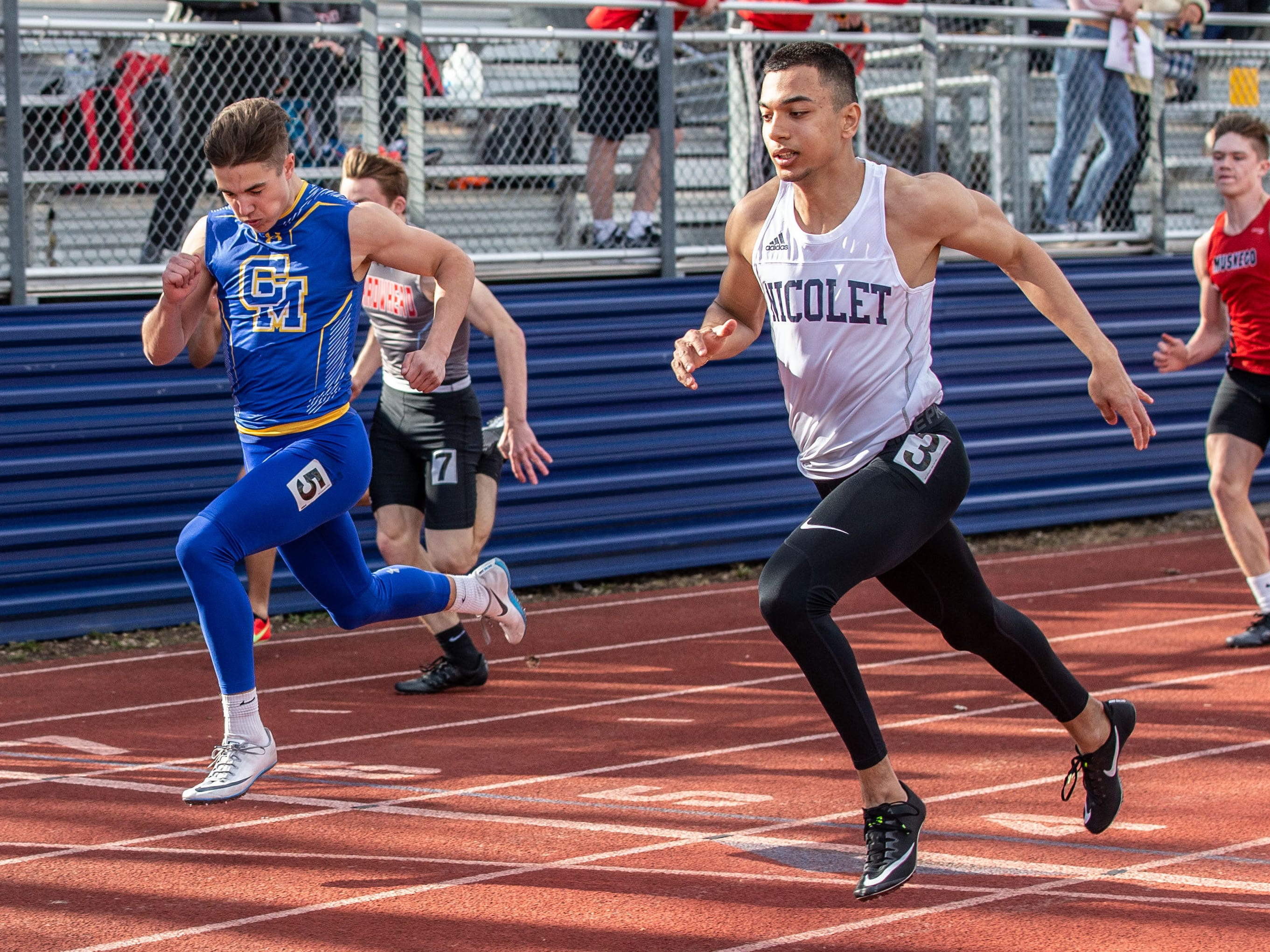 Nicolet's Arslan Jumabayev (3) races Catholic Memorial's Joe Sikma (5) to the finish in the 100 meter dash during the Mike Gain 50th Annual Spartan Invitational at Brookfield East on Tuesday, April 9, 2019. Jumabayev won with a time of 11.17 and Sikma placed second with a time of 11.24.