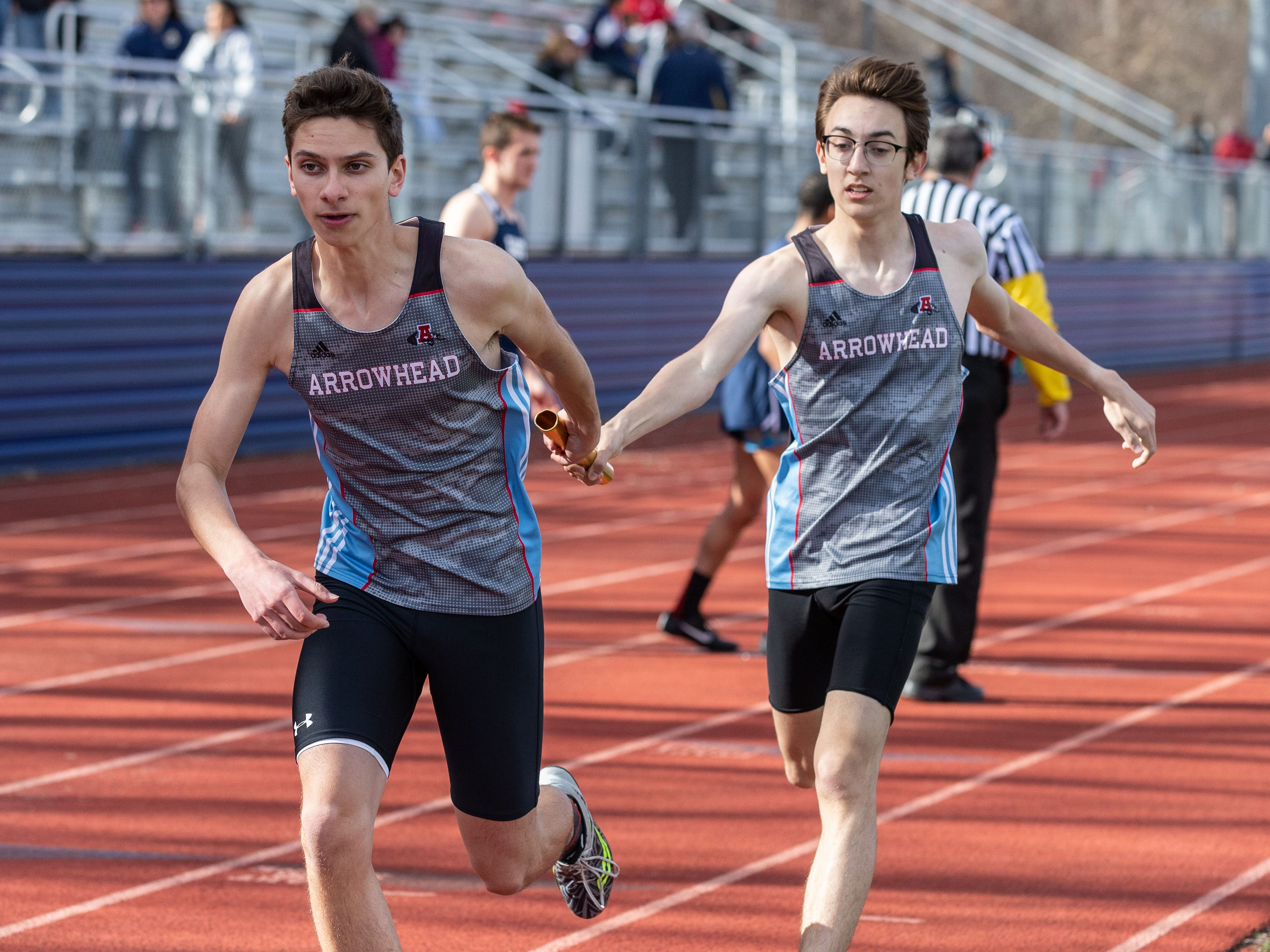 Arrowhead's Taylor Smith (left) takes the baton from Alex Noll in the 4x800 meter relay during the Mike Gain 50th Annual Spartan Invitational at Brookfield East on Tuesday, April 9, 2019.