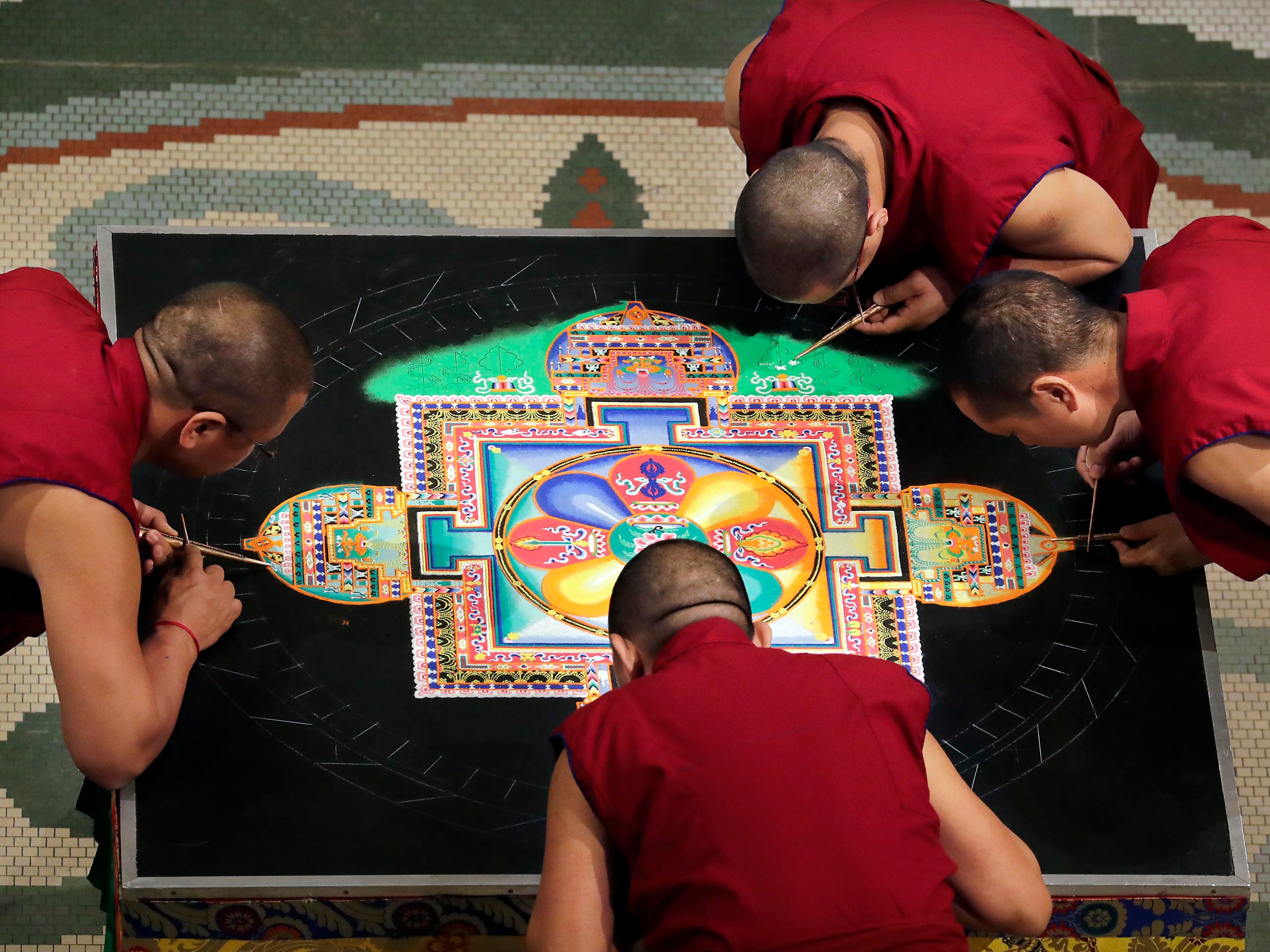 """Buddhist monks from the Drepung Loseling Monastery, mix bowls of colorful sand and use funnels to apply the sand and create a  sand mandala in the center of Milwaukee's City Hall, Thursday, April 11, 2019.   The mandala represents the world in its divine form; on the inner level, they represent a map by which the ordinary human mind is transformed into enlightened mind; and on the secret level, they depict the primordially perfect balance of the subtle energies of the body and the clear light dimension of the mind. The creation of a sand painting is said to effect purification and healing on these three levels.  The display ends with a closing ceremony Friday at 5 p.m. where the sand """"painting"""" will be destroyed and vials of sand shared with attendees. For more information go to www.earlymusicnow.org"""