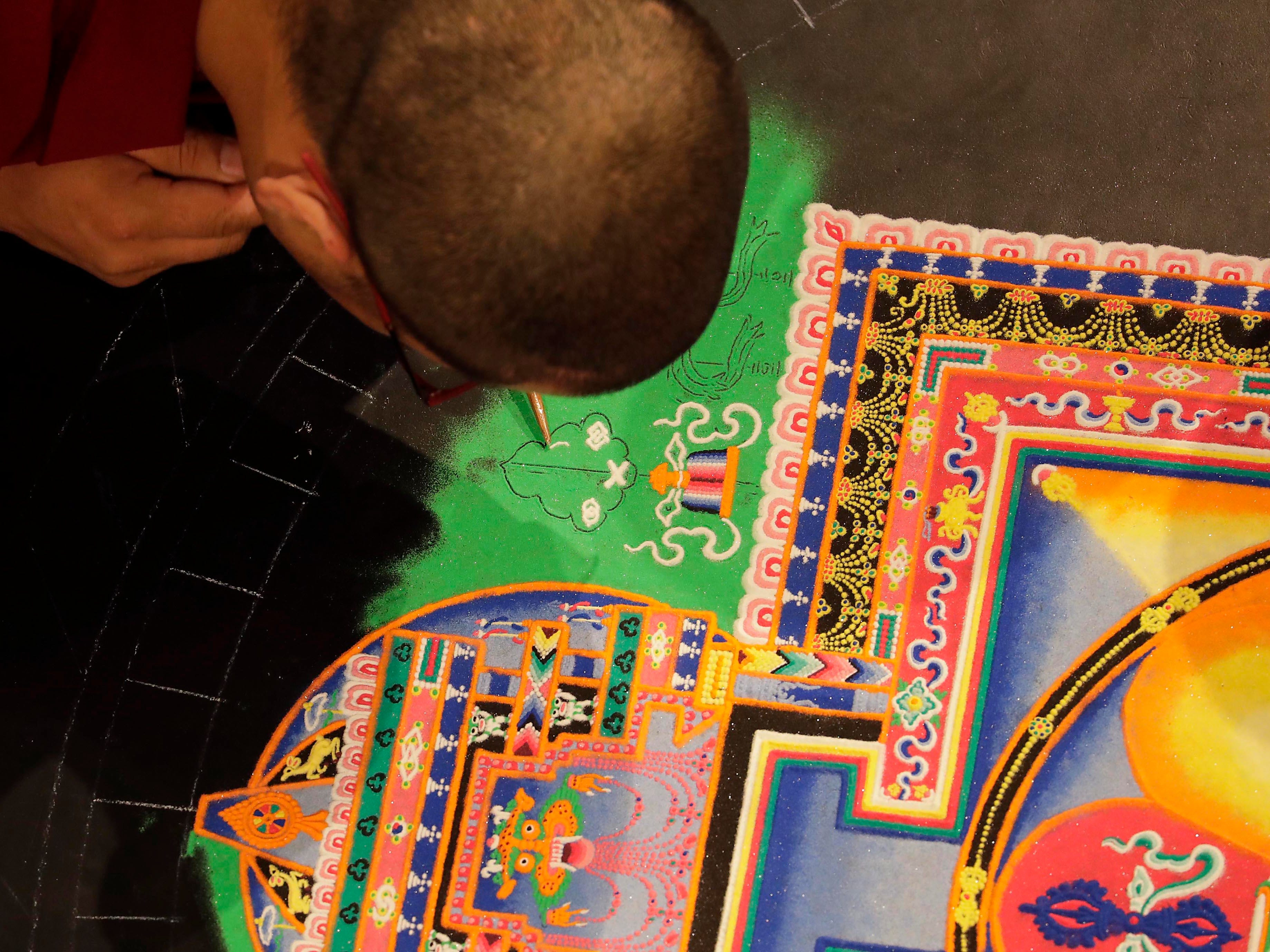 """Lobsang Tsarchin, a Buddhist monk, used a funnel to apply small amounts of sand into a form creating a mandala. Buddhist monks from the Drepung Loseling Monastery, use the colorful sand and use funnels to apply the sand and create a  sand mandala in the center of Milwaukee's City Hall, Thursday, April 11, 2019.   The mandala represents the world in its divine form; on the inner level, they represent a map by which the ordinary human mind is transformed into enlightened mind; and on the secret level, they depict the primordially perfect balance of the subtle energies of the body and the clear light dimension of the mind. The creation of a sand painting is said to effect purification and healing on these three levels.  The display ends with a closing ceremony Friday at 5 p.m. where the sand """"painting"""" will be destroyed and vials of sand shared with attendees. For more information go to www.earlymusicnow.org"""