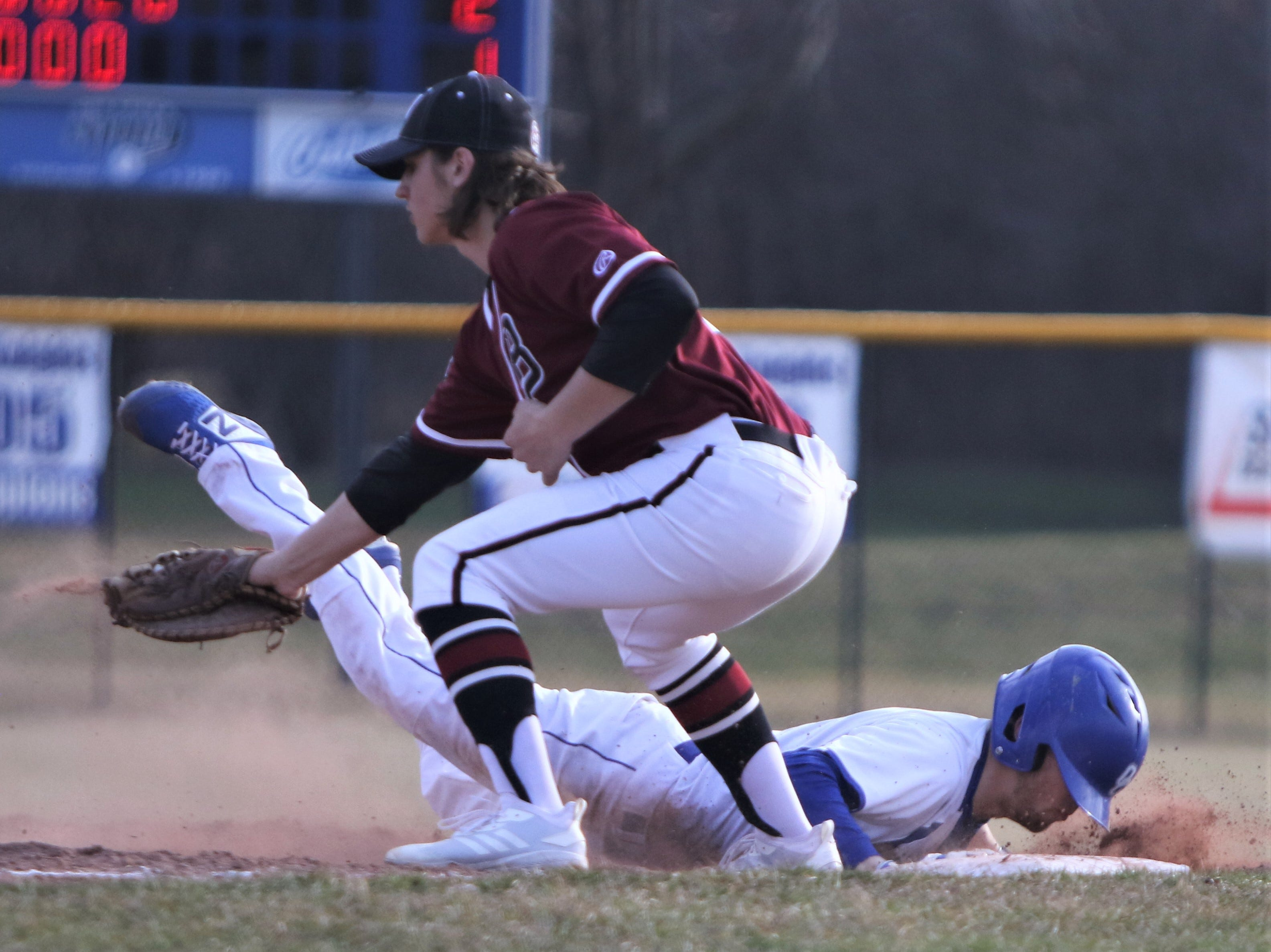 Oak Creek junior Aaron Smith dives back safely into first base on a pickoff attempt against Kenosha Bradford on April 9, 2019.