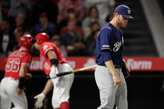 Brewers starting pitcher Brandon Woodruff walks away as Los Angeles' Kole Calhoun, background left, is greeted by Albert Pujols after Calhoun scored on a single by Justin Bour during the third inning.