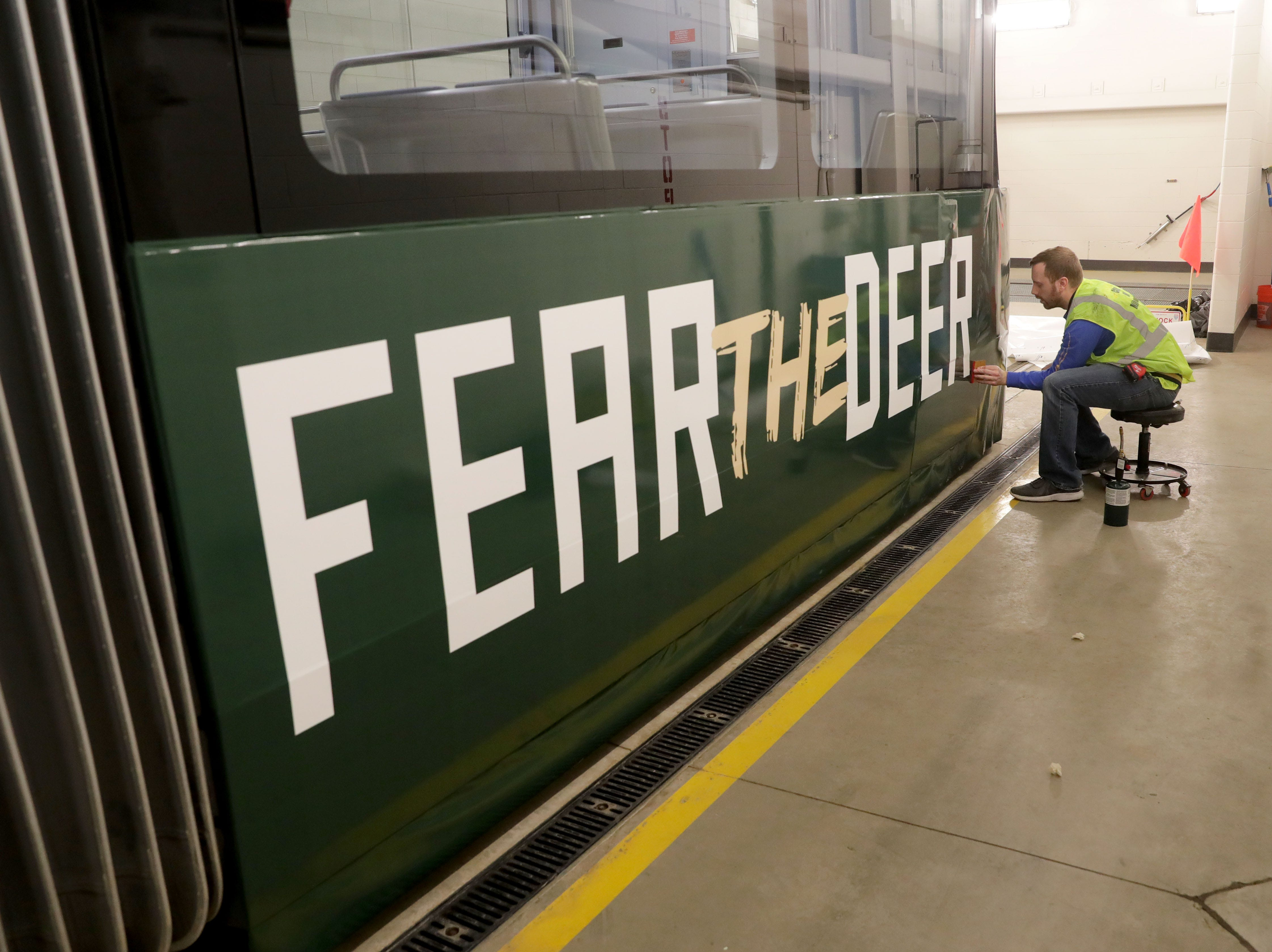 (OK FOR FRIDAY 4/12 PRINT - ONLINE EMBARGO UNTIL 10:45 FRIDAY 4/12) Troy Heinzel with Signs and Lines by Stretch work on attaching a logo to the outside of the streetcar.  One of Milwaukee's streetcars, known as The Hop is wrapped in Milwaukee Bucks colors in support of the Bucks playoff run in Milwaukee on Thursday, April 11, 2019. In addition to the exterior flair, the interior has been fitted with a replica Bucks court on the floor complete with life-size player footprints.   Photo by Mike De Sisti/Milwaukee Journal Sentinel