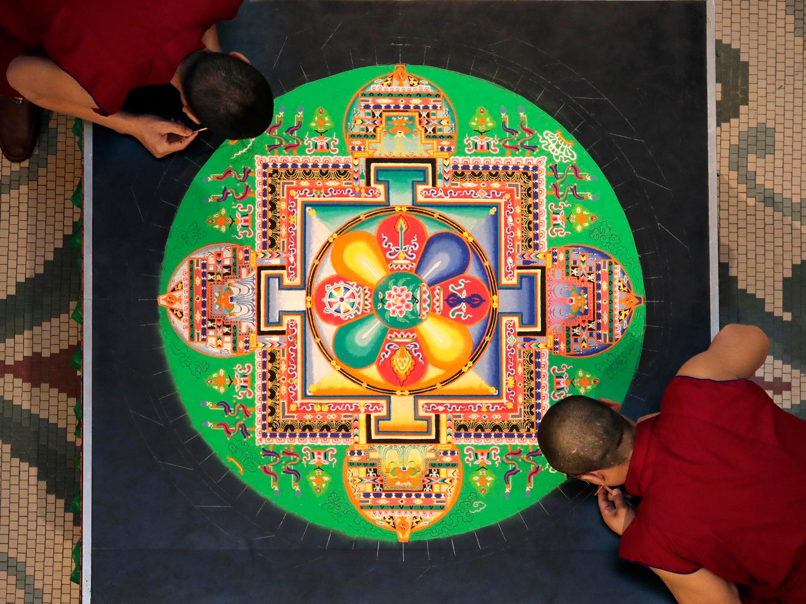 Buddhist monks from the Drepung Loseling Monastery, mix bowls of colorful sand and use funnels to apply the sand and create a  sand mandala in the center of Milwaukee's City Hall, Thursday, April 11, 2019.