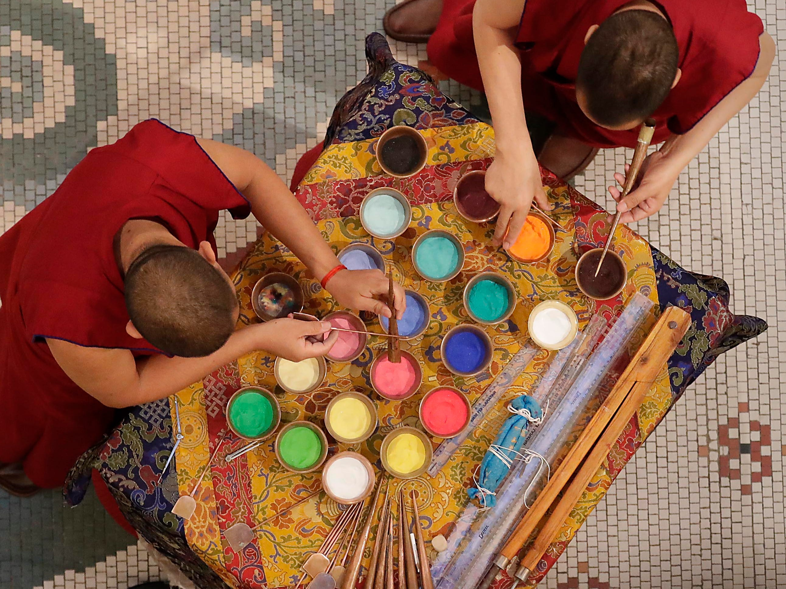 Buddhist monks from the Drepung Loseling Monastery, mix bowls of colorful sand and use narrow metal funnels to apply the sand and create a  sand mandala in the center of Milwaukee's City Hall, Thursday, April 11, 2019.