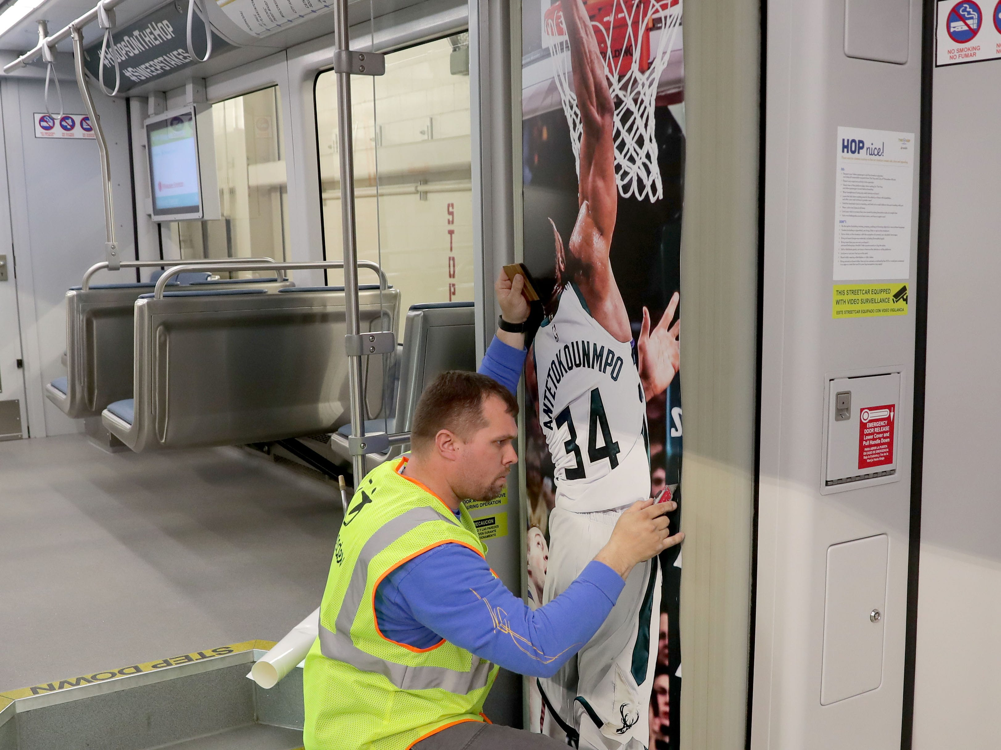 (OK FOR FRIDAY 4/12 PRINT - ONLINE EMBARGO UNTIL 10:45 FRIDAY 4/12)  Matt Callies with Signs and Lines by Stretch works on placing a Giannis Antetokounmpo poster up. One of Milwaukee's streetcars, known as The Hop is fitted with a replica Bucks court on the floor in support of the Bucks playoff run in Milwaukee on Thursday, April 11, 2019. In addition to the interior flair, the exterior was being wrapped in Milwaukee Bucks colors.  Photo by Mike De Sisti/Milwaukee Journal Sentinel
