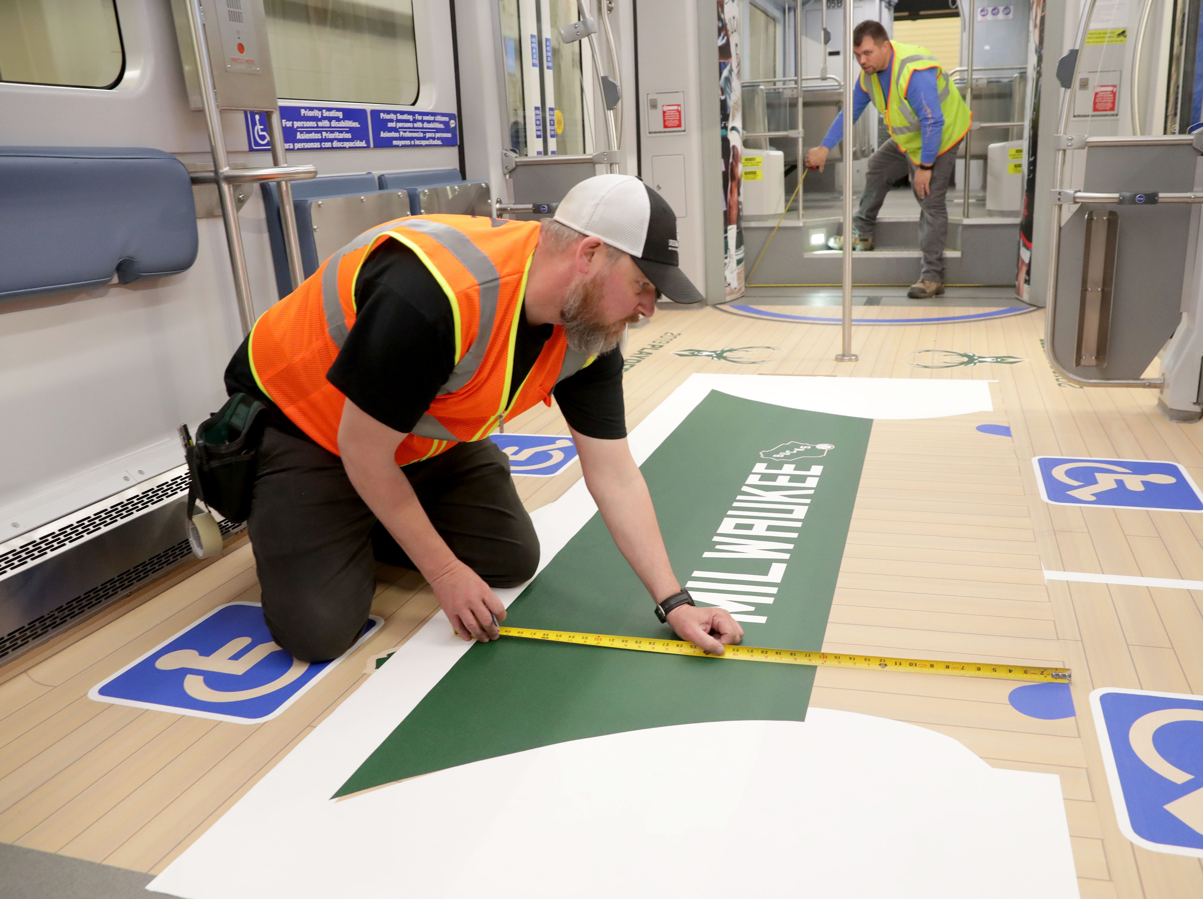 (OK FOR FRIDAY 4/12 PRINT - ONLINE EMBARGO UNTIL 10:45 FRIDAY 4/12) Eric Ewald (left) with Signs and Lines by Stretch measures a logo before placing it on the floor as co-worker Matt Callies take a measurement.  Bucks decoration up on the ceiling of the streetcar. One of Milwaukee's streetcars, known as The Hop is fitted with a replica Bucks court on the floor in support of the Bucks playoff run in Milwaukee on Thursday, April 11, 2019. In addition to the interior flair, the exterior was being wrapped in Milwaukee Bucks colors.  Photo by Mike De Sisti/Milwaukee Journal Sentinel