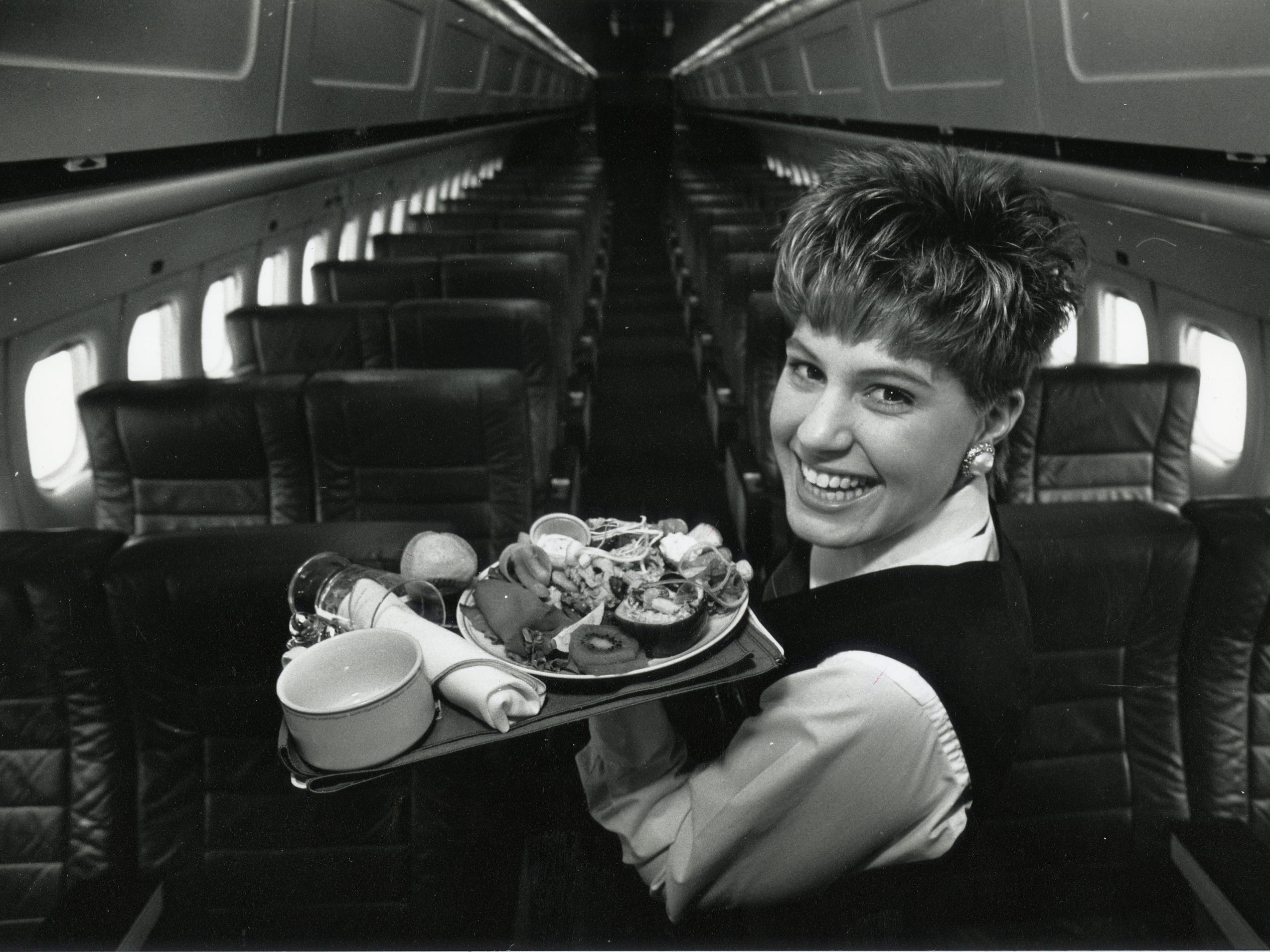 "In 1990 Nicole Pecha, a Midwest Express flight attendant, displays a meal that will be served to passengers on a flight to Boston. The airline's premium meals are one reason that Consumer Reports Travel Letter chose it as ""best US airline overall"" in the publication's January issue."