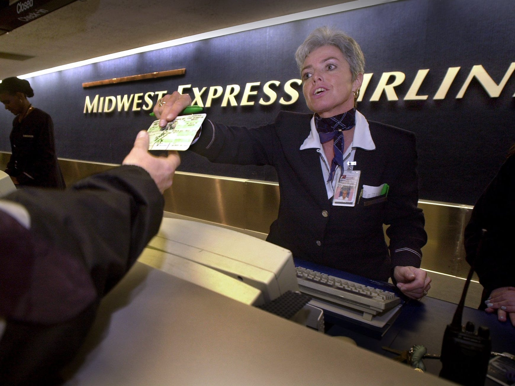 Deb Jewett, a customer service supervisor for Midwest Express Airlines, works with customers at Mitchell International Airport. Midwest Express Airlines warned investors  that it would post a loss for the fourth quarter. The loss is only the airline's second since it became publicly-traded in 1995.