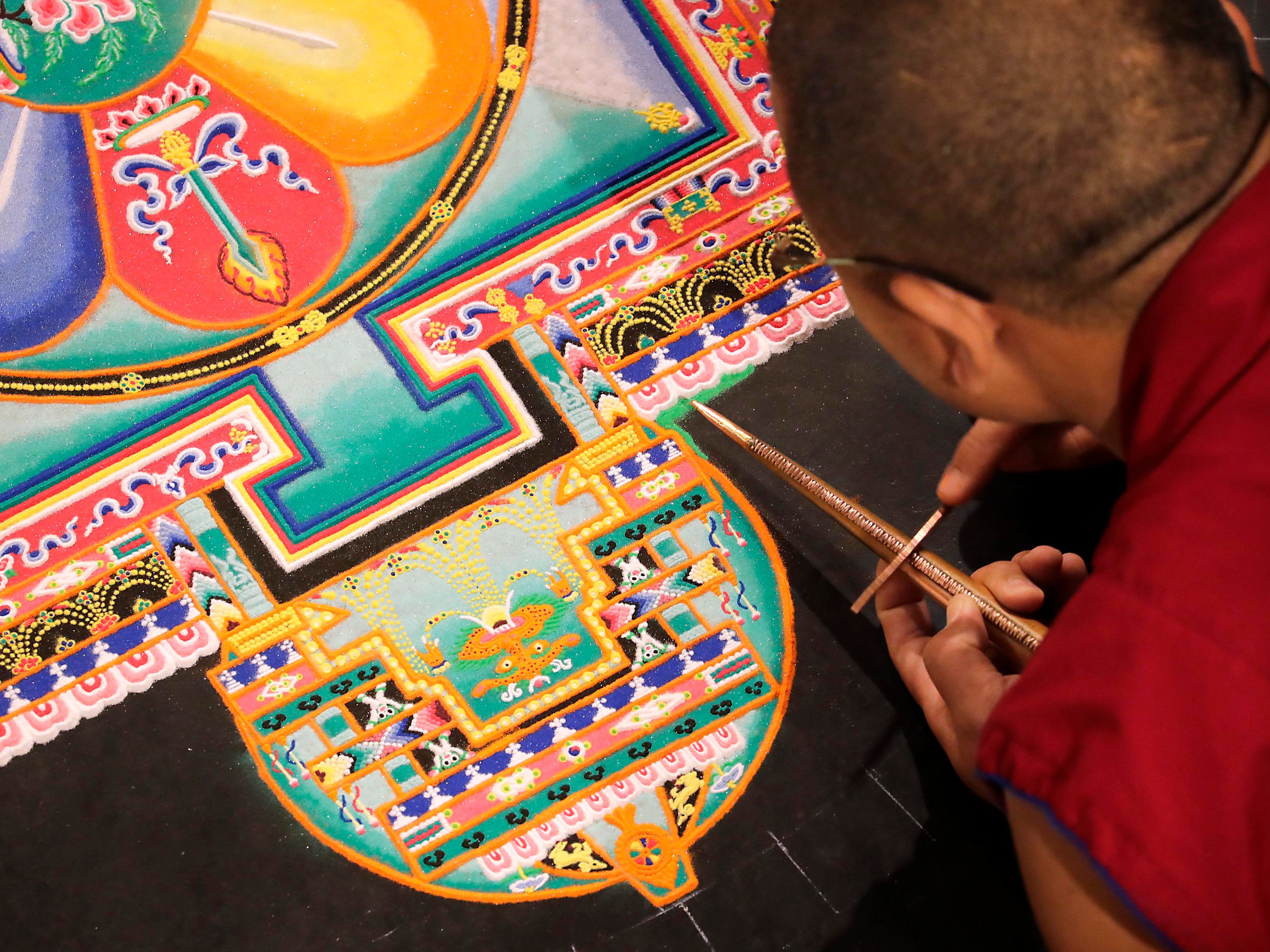 """Tenzin Sangay, a Buddhist monk, creates vibration of sand in a metal funnel that drops millions of grains of sand to crate the mandala. Buddhist monks from the Drepung Loseling Monastery, mix bowls of colorful sand and use funnels to apply the sand and create a  sand mandala in the center of Milwaukee's City Hall, Thursday, April 11, 2019.   The mandala represents the world in its divine form; on the inner level, they represent a map by which the ordinary human mind is transformed into enlightened mind; and on the secret level, they depict the primordially perfect balance of the subtle energies of the body and the clear light dimension of the mind. The creation of a sand painting is said to effect purification and healing on these three levels.  The display ends with a closing ceremony Friday at 5 p.m. where the sand """"painting"""" will be destroyed and vials of sand shared with attendees. For more information go to www.earlymusicnow.org"""