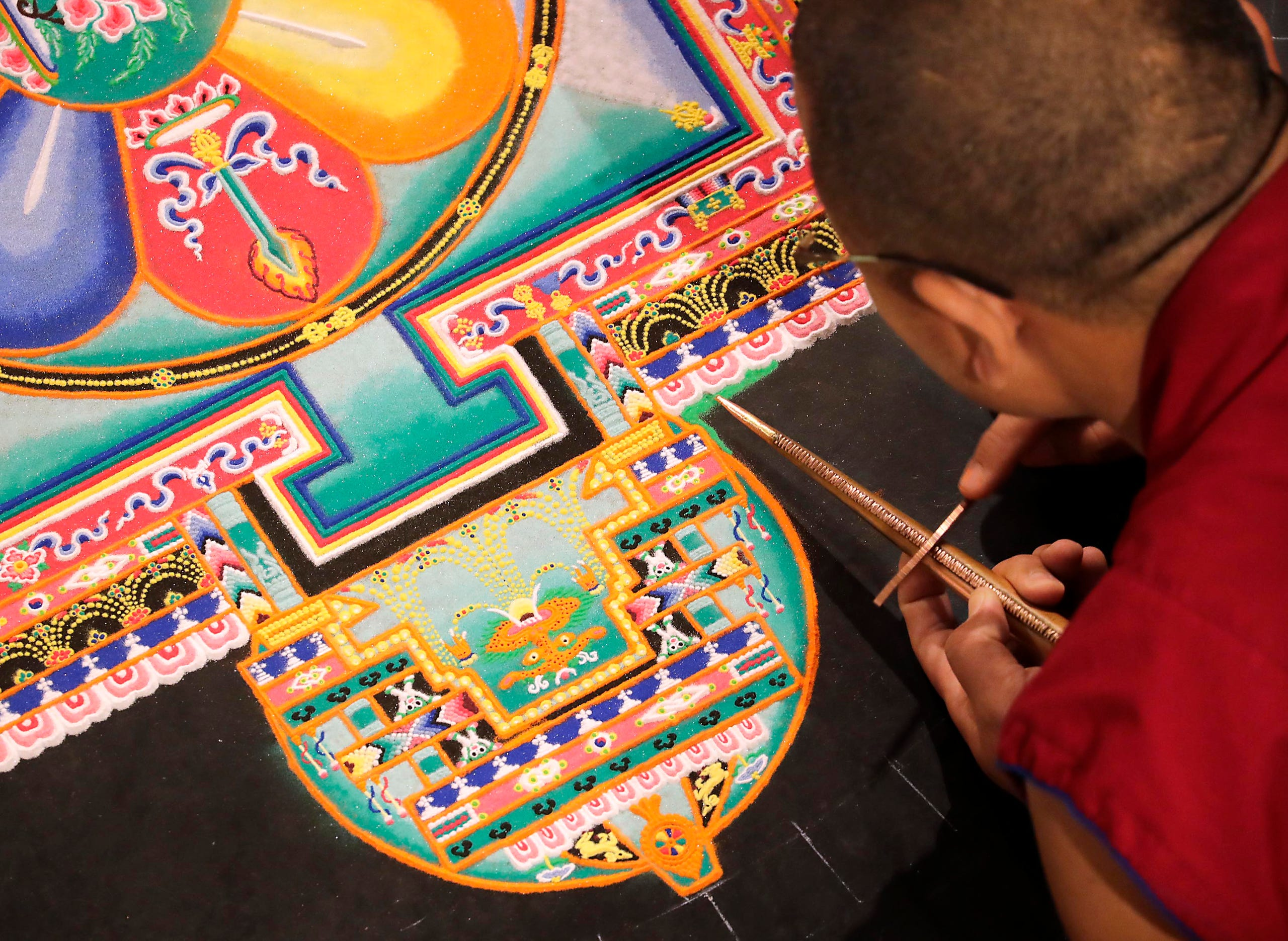 See Buddhist monks create a sand mandala in the center of
