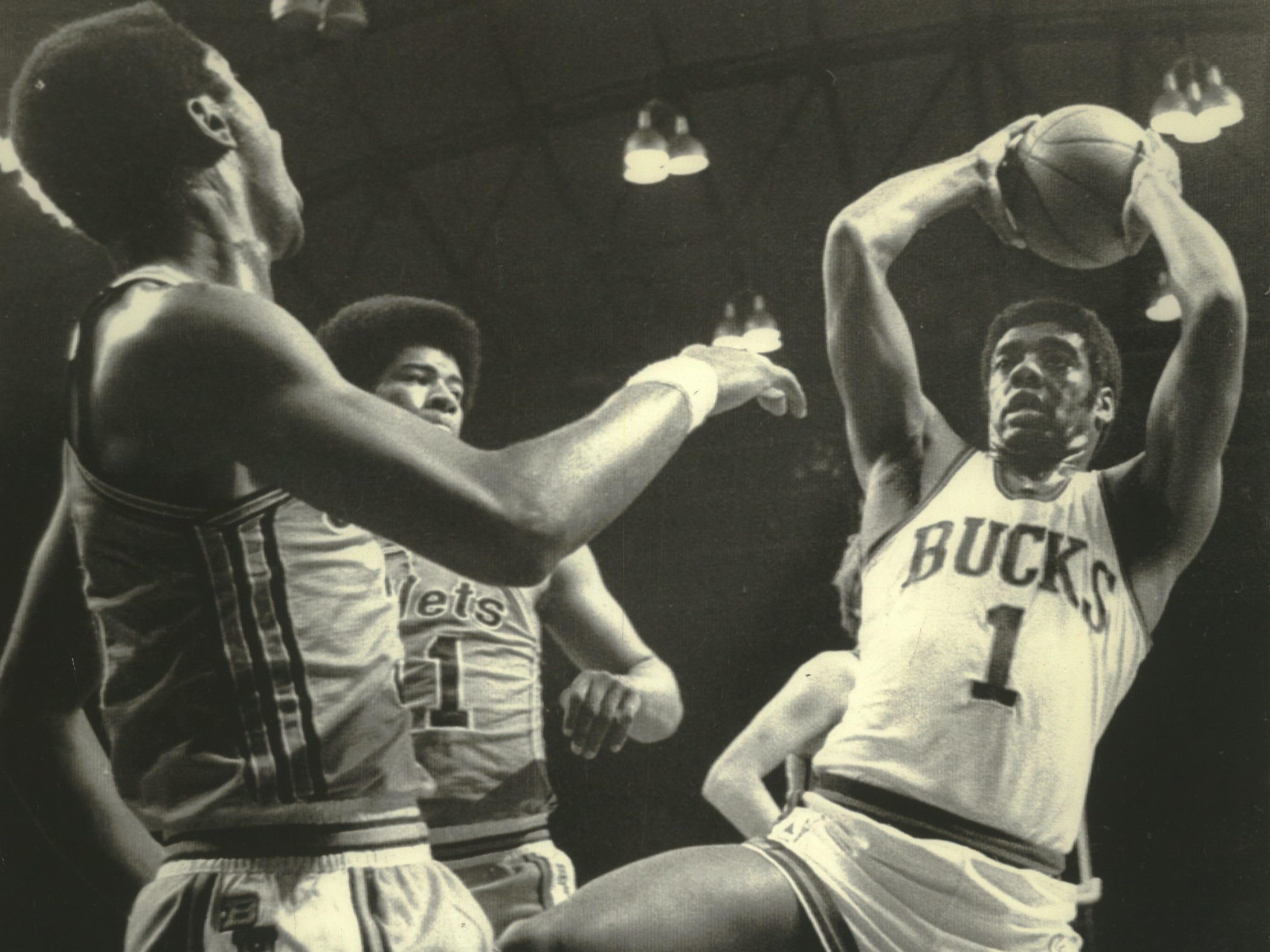 1971: Oscar Robertson (right) pulls down a rebound for the Milwaukee Bucks during Game 1 of the NBA finals against the Baltimore Bullets on April 21, 1971. Looking on are the Bullets' Fred Carter (left) and Wes Unseld. The Bucks beat the Bullets in four straight to win their first NBA championship.