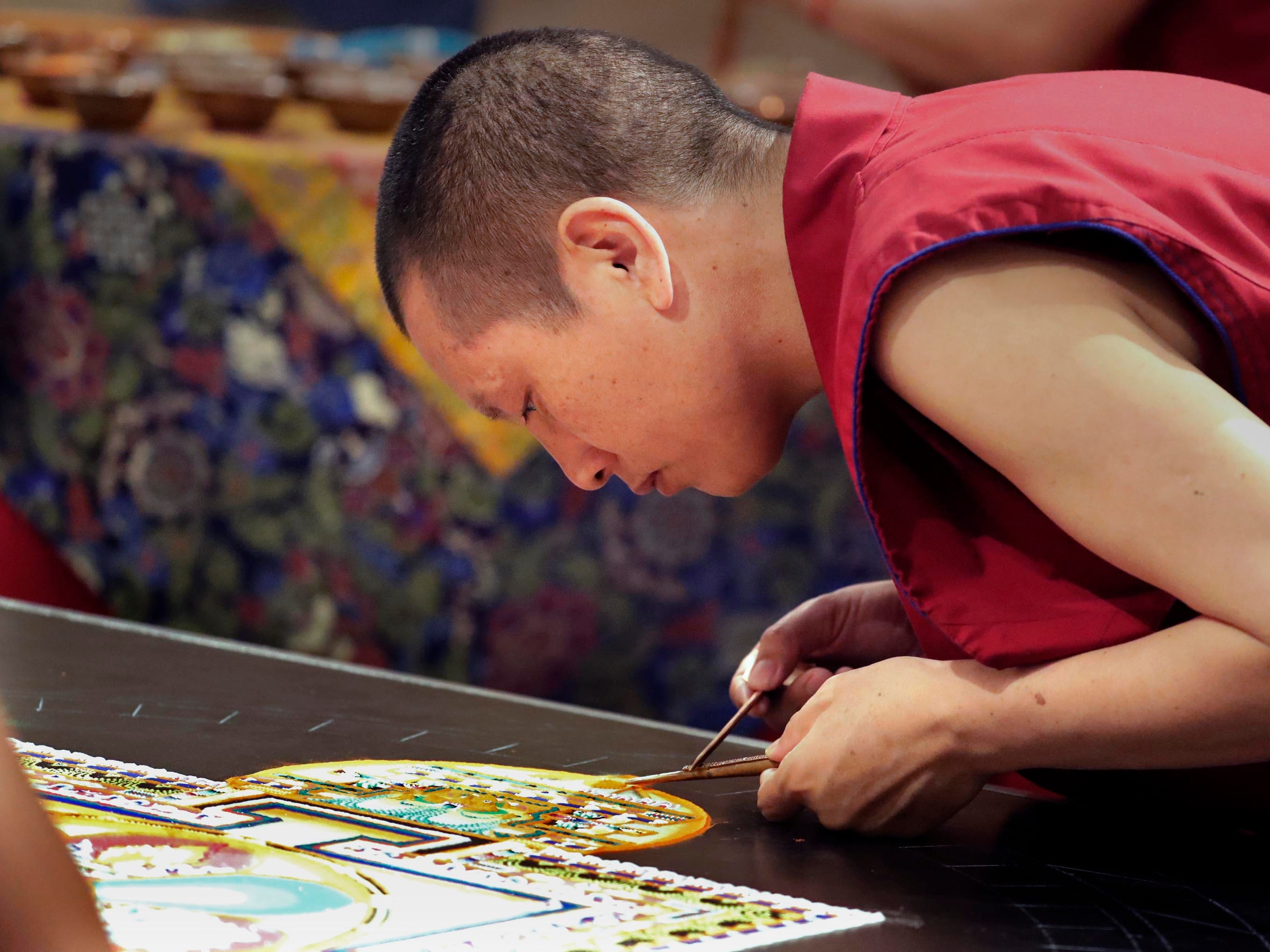 """Lobsang Dorjee, a Buddhist monk, applies sand to create an intricate portion of the mandala. Buddhist monks from the Drepung Loseling Monastery, mix bowls of colorful sand and use funnels to apply the sand and create a  sand mandala in the center of Milwaukee's City Hall, Thursday, April 11, 2019.   The mandala represents the world in its divine form; on the inner level, they represent a map by which the ordinary human mind is transformed into enlightened mind; and on the secret level, they depict the primordially perfect balance of the subtle energies of the body and the clear light dimension of the mind. The creation of a sand painting is said to effect purification and healing on these three levels.  The display ends with a closing ceremony Friday at 5 p.m. where the sand """"painting"""" will be destroyed and vials of sand shared with attendees. For more information go to www.earlymusicnow.org"""