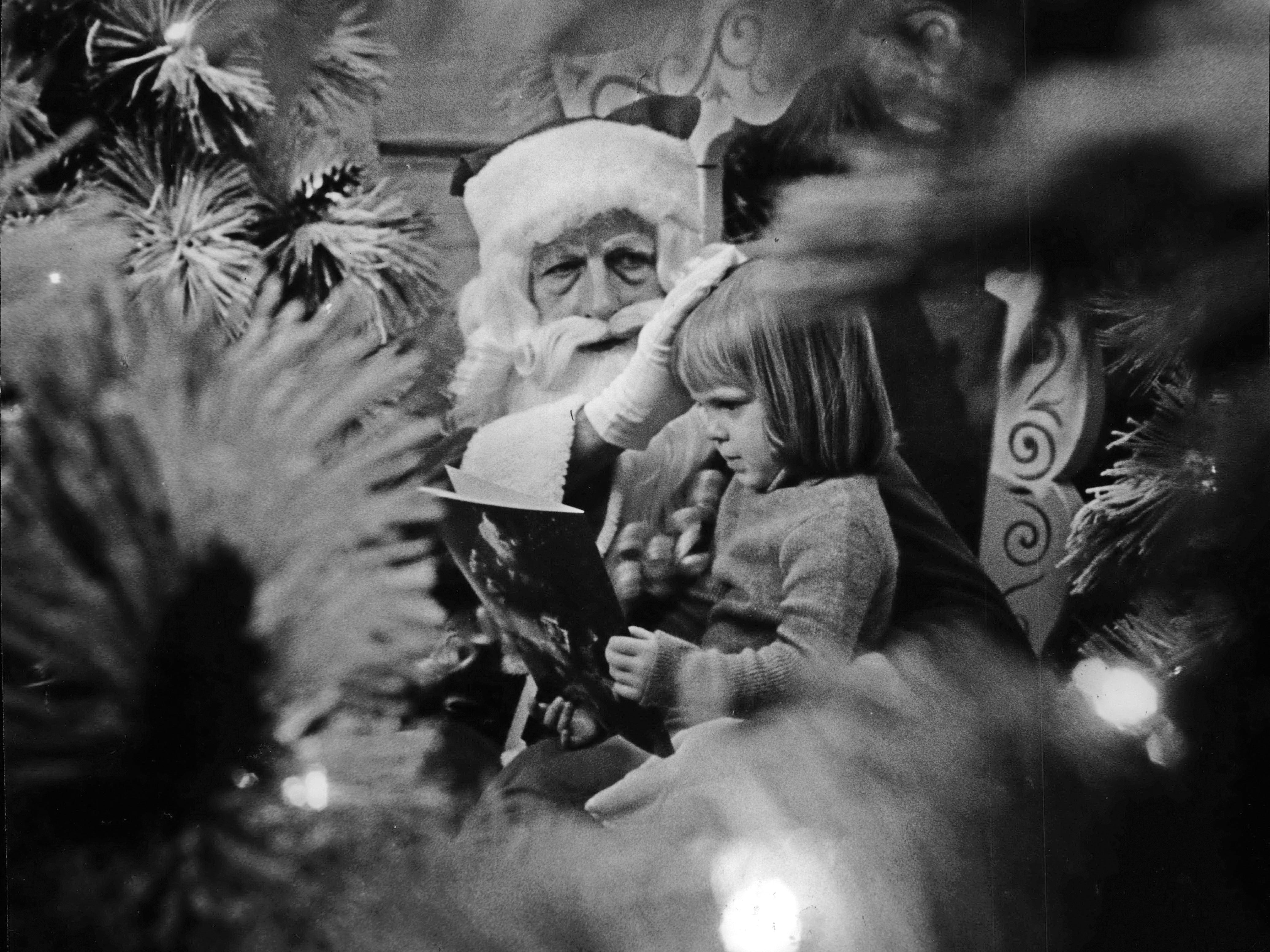 December, 1981: A little girl seemed more interested in her Christmas book than in Santa during a visit with Mr. Claus at Northridge Shopping Center.